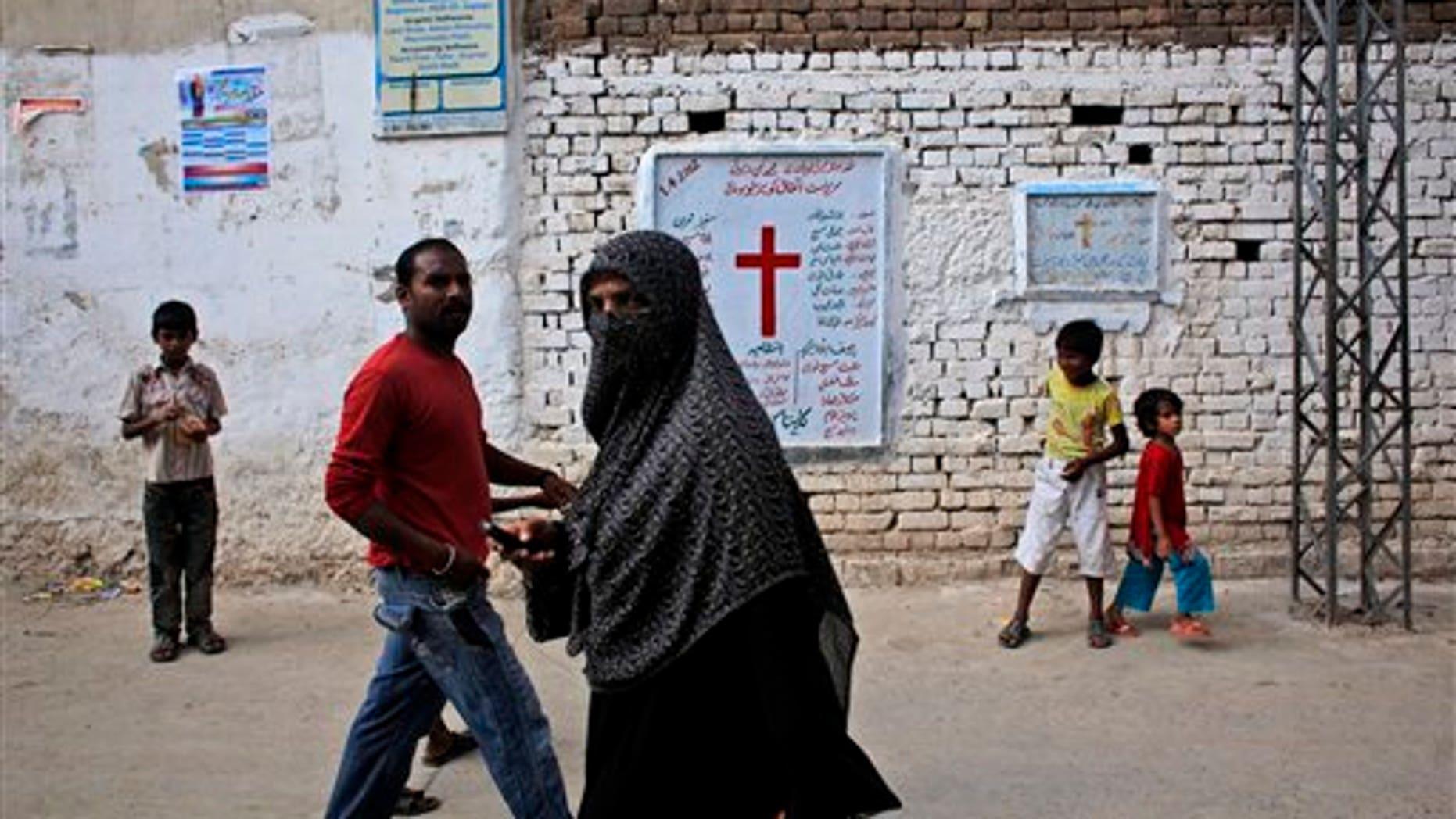 Aug. 30, 2012: Pakistanis walk in a Christian neighborhood in Islamabad, Pakistan.