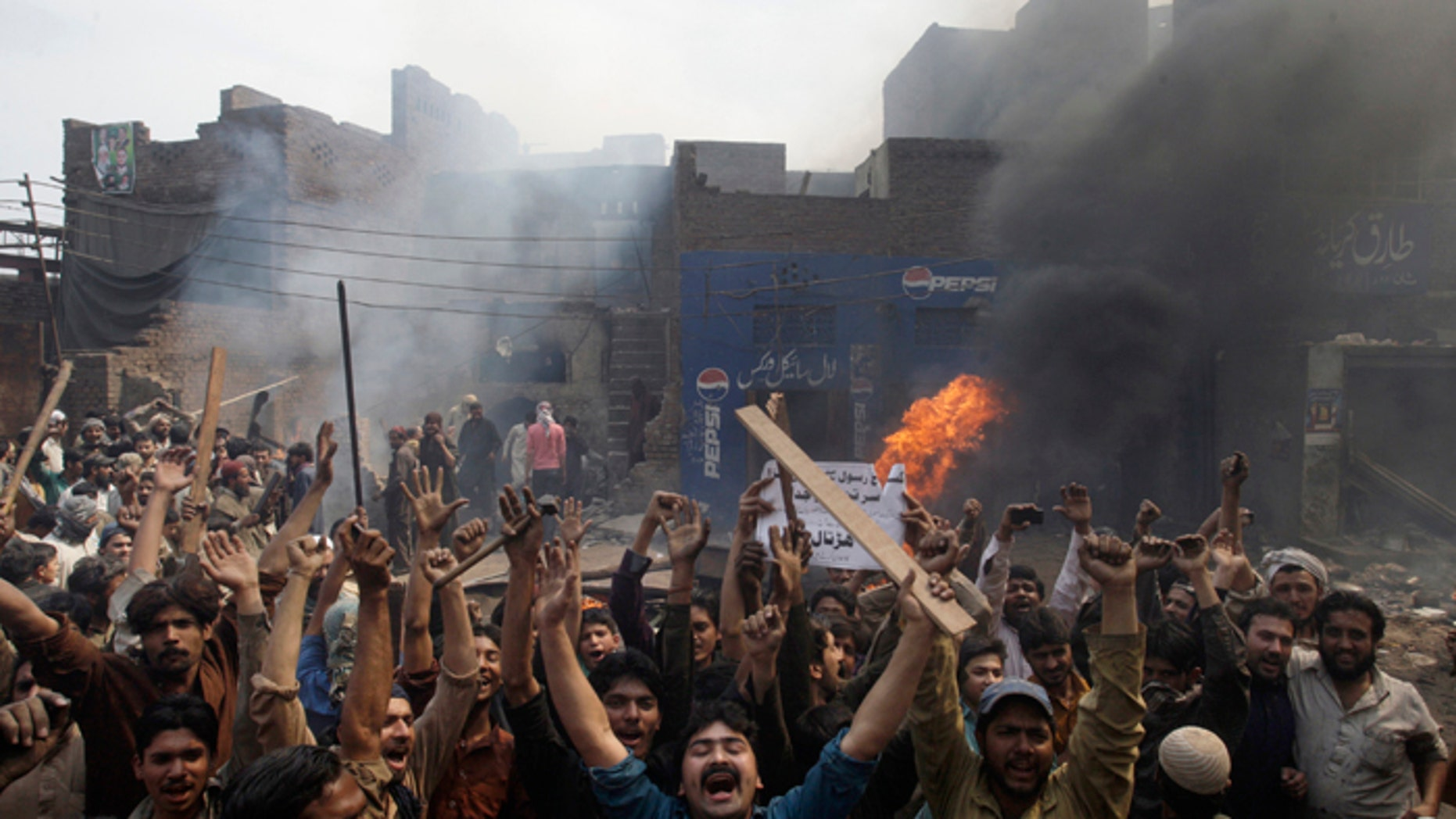 An angry mob reacts after burning Christian houses in Lahore, Pakistan, on Saturday. (AP Photo/K.M. Chaudary)