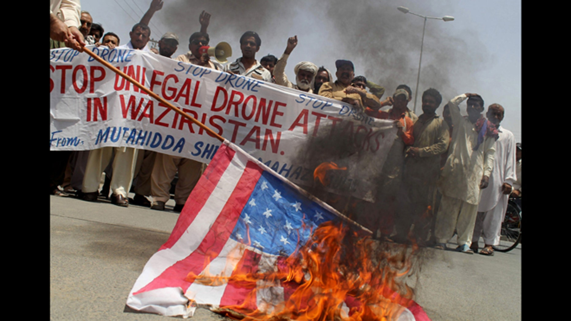 May 30, 2013: Pakistani protesters burn a representation of a U.S. flag to condemn a drone attack in the Pakistani tribal area of Waziristan which killed Taliban leader Waliur Rehman in Multan, Pakistan.