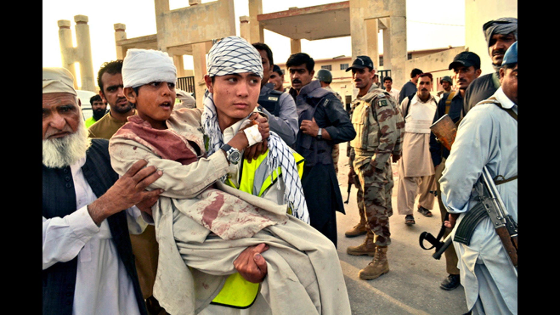 June 15, 2013: A Pakistani boy who was injured by gunmen is carried to a vehicle outside a hospital in Quetta, Pakistan. Gunmen took over parts of a hospital in southwestern Pakistan Saturday after a bomb went off inside its emergency room, officials said.