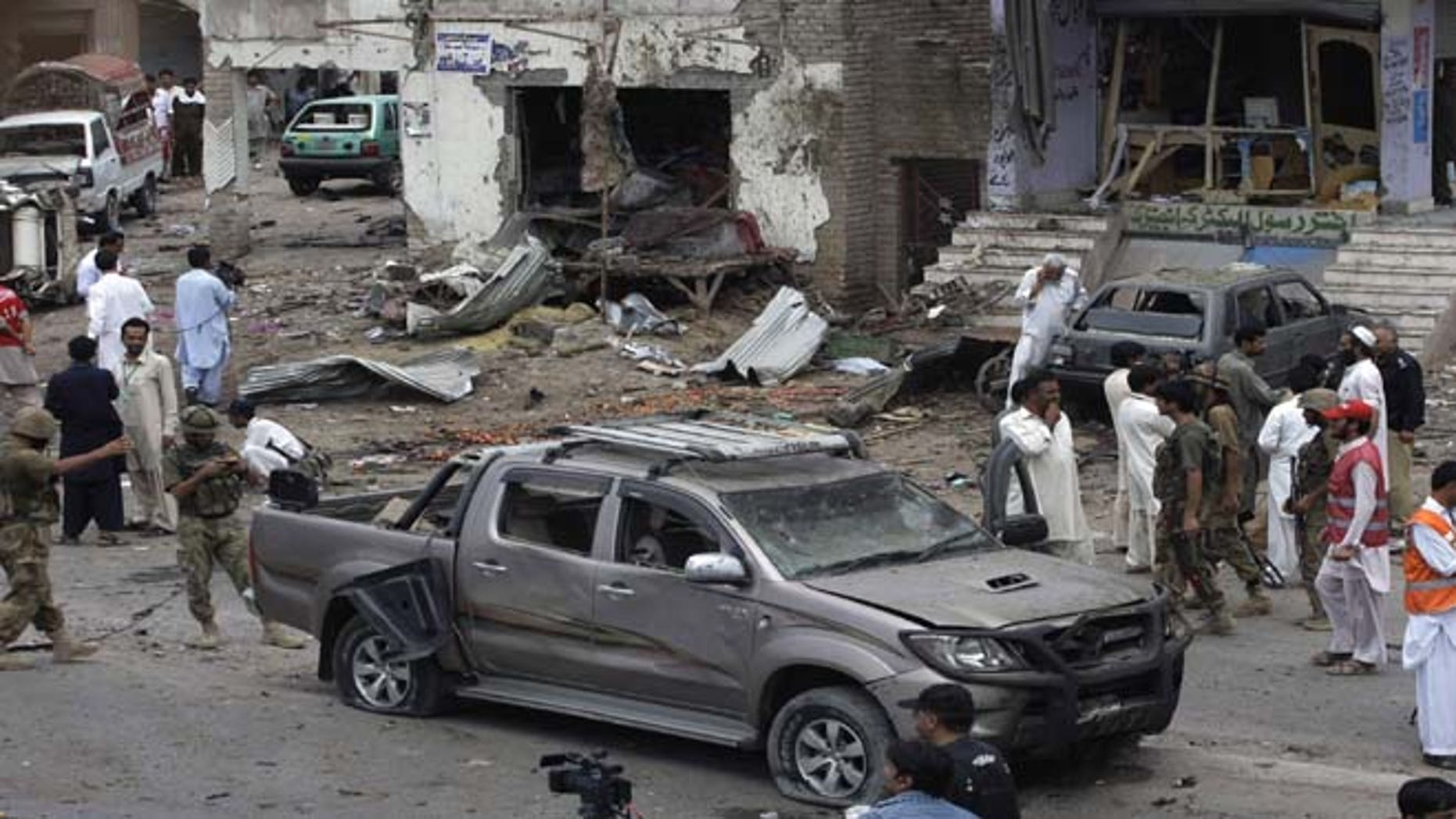 June 30, 2013: Pakistani security officials and rescue workers examine the site of car bombing on the outskirts of Peshawar, Pakistan. A car bomb exploded as a convoy of paramilitary troops passed through the outskirts of the northwest Pakistani city of Peshawar, killing more than a dozen people and wounding scores of others, police said.