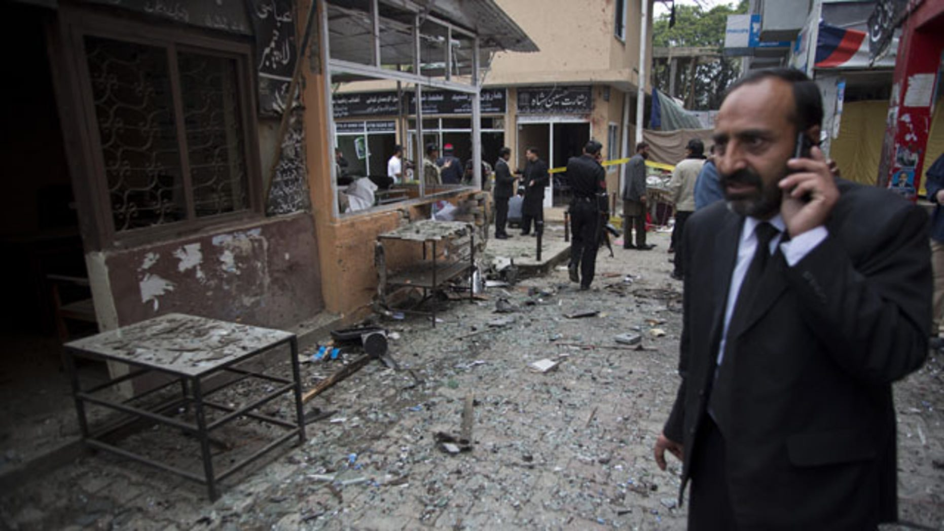 March 3, 2014: A Pakistani lawyer talks on his mobile phone at the site of a suicide attack in a court complex in Islamabad, Pakistan. Two suicide bombers blew themselves up at the complex on Monday, killing 11 people and wounding dozens in a rare terror attack in the heart of Islamabad, officials said. (AP Photo/B.K. Bangash)