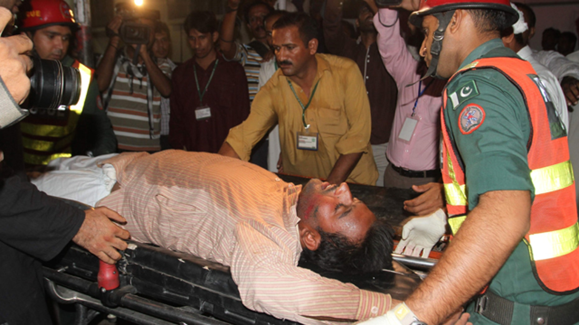 October 10, 2014: Pakistani rescue workers rush an injured person to a local hospital in Multan. (AP Photo/Asim Tanveer)