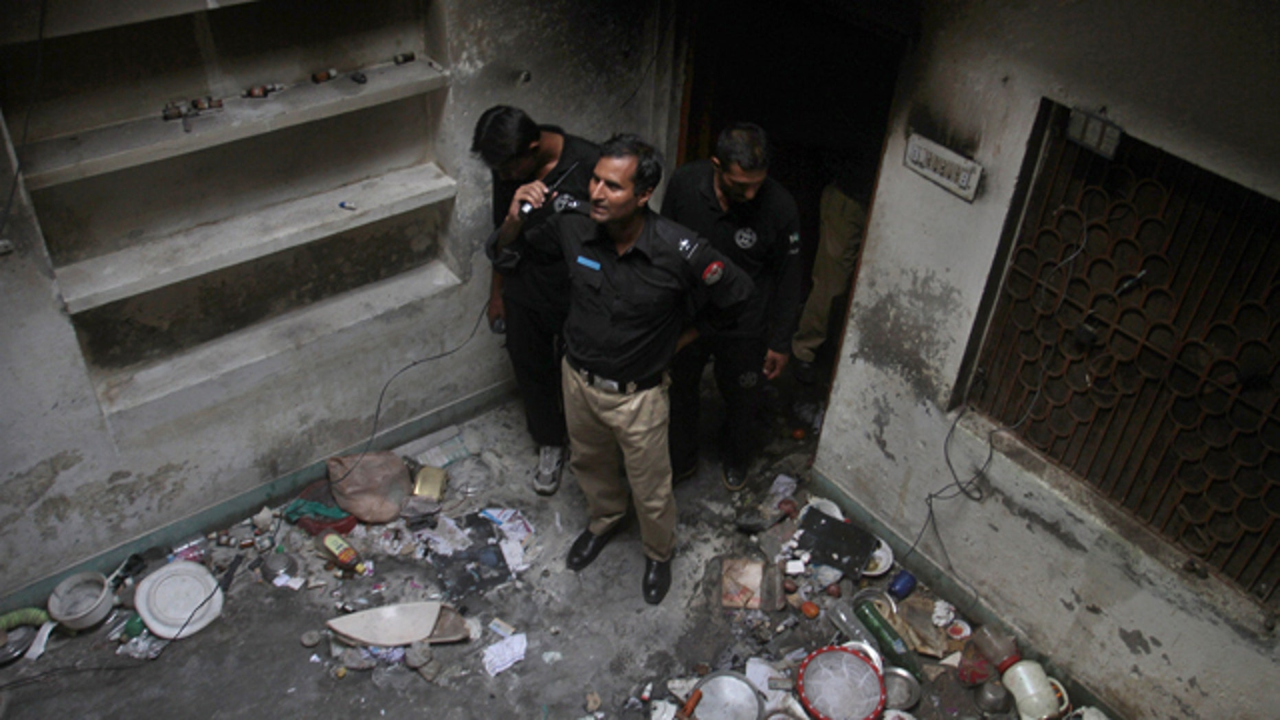 July 28, 2014: Pakistani police officers examine a house of a family belonging to the Ahmadi sect, which was torched by angry mob in Gujranwala, Pakistan. (AP Photo/K.M. Chaudary)