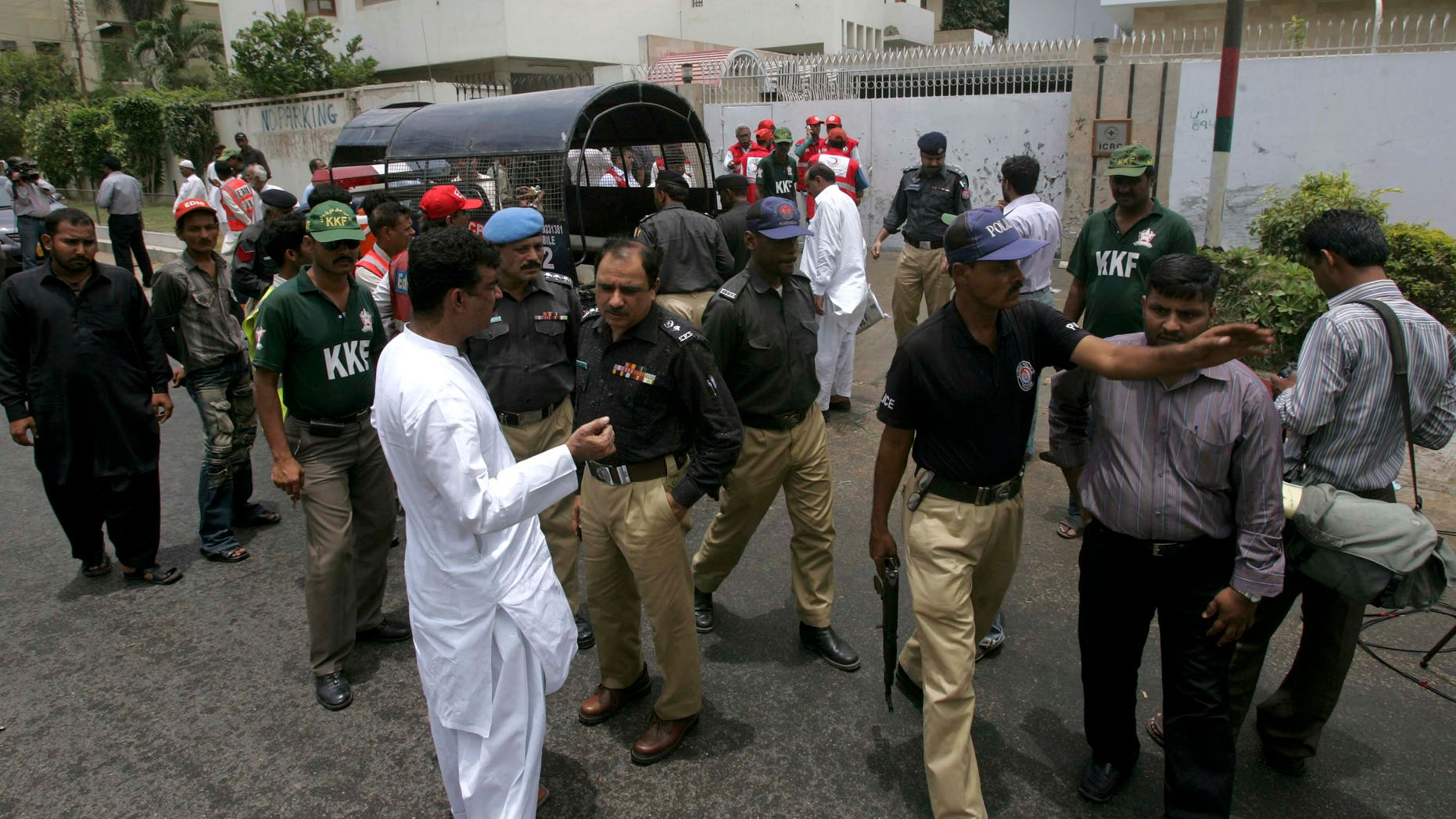 June 25: Pakistani police officer gather at the site of an explosion outside the office of International Committee of the Red Cross in Karachi, Pakistan. A planted bomb partially exploded as it was being defused next to a Red Cross office in Pakistan's south, but no one was hurt, police said.