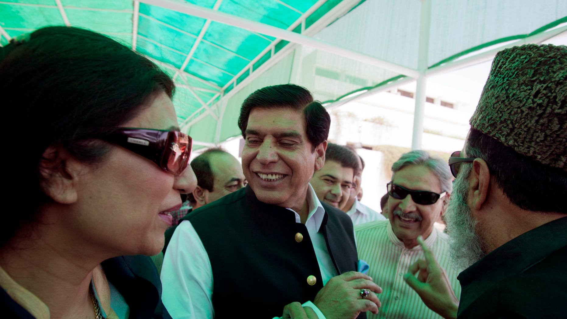 June 21, 2012: In this photo, Pakistani lawmakers greet Raja Pervaiz Ashraf, second from left, as he leaves the Parliament in Islamabad, Pakistan after filing his nomination as a  candidate for the premiership.