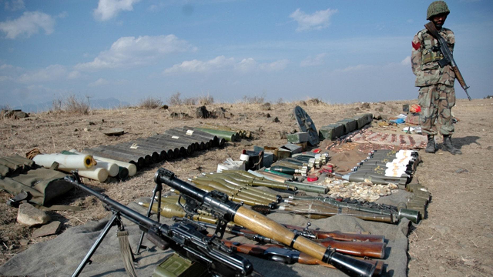 Pakistan army soldier stands next to ammunition seized from militants in Wana of Pakistani tribal region of Waziristan.