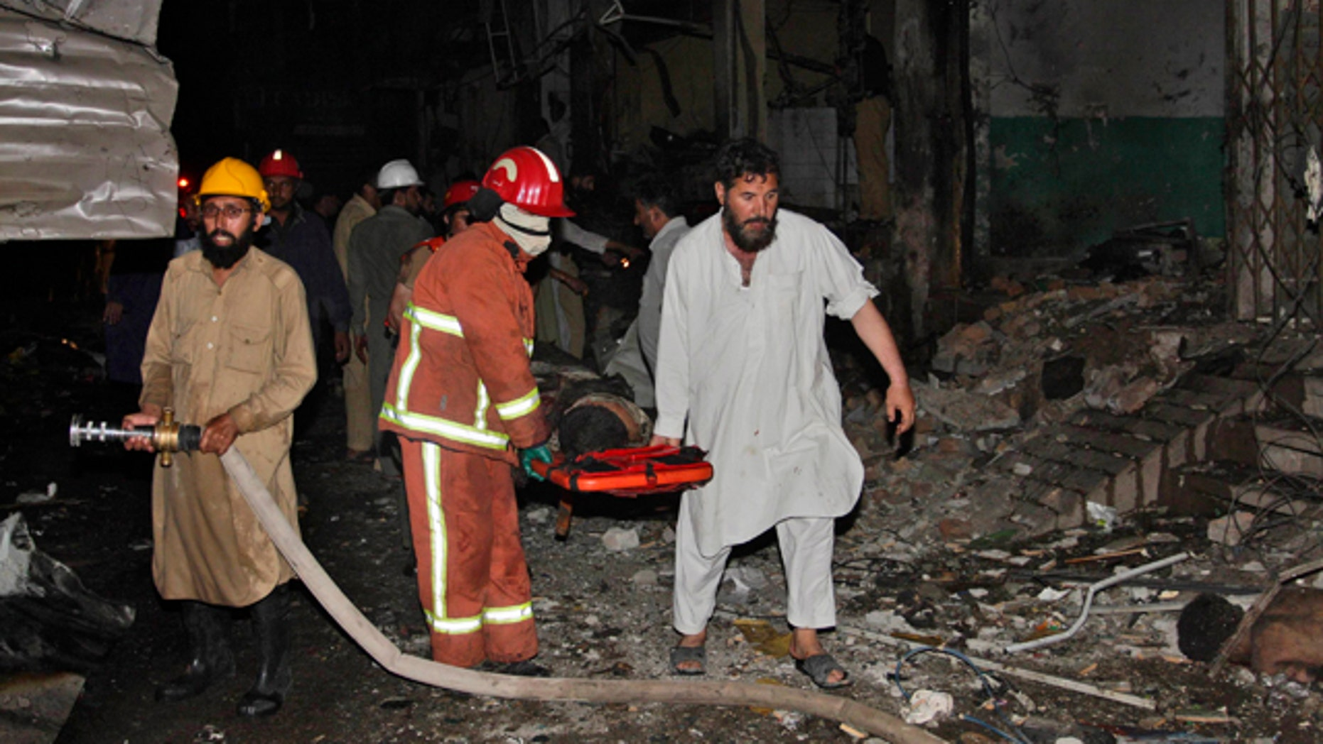 June 12: Pakistani rescue workers carry away a wounded man from the site of an explosion in Peshawar, Pakistan.