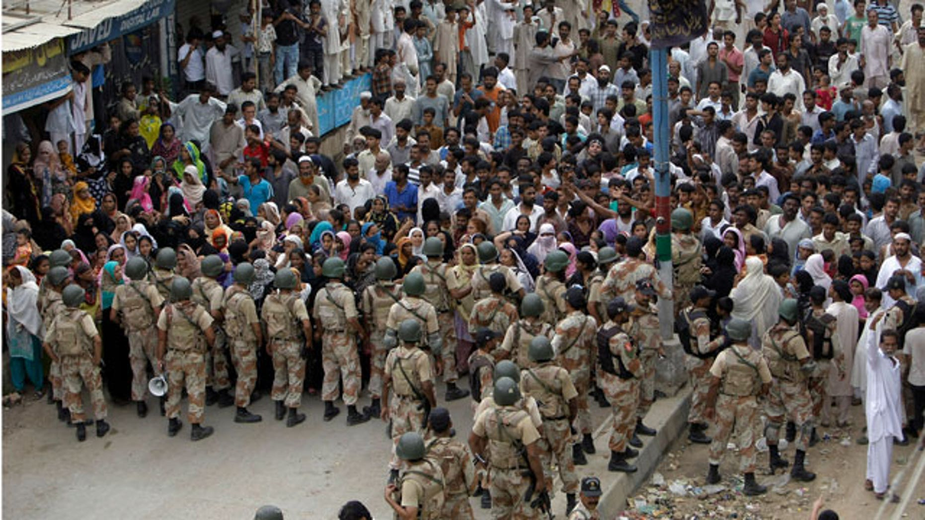 Paramilitary troops try to control a crowd gather to complain their problems after security forces took control of a troubled area of Karachi, Pakistan on Saturday, July 9, 2011. Gunshots rattled Pakistan's largest city Saturday as authorities scrambled to bring an end to political and ethnic violence that has claimed at least 93 lives in five days.