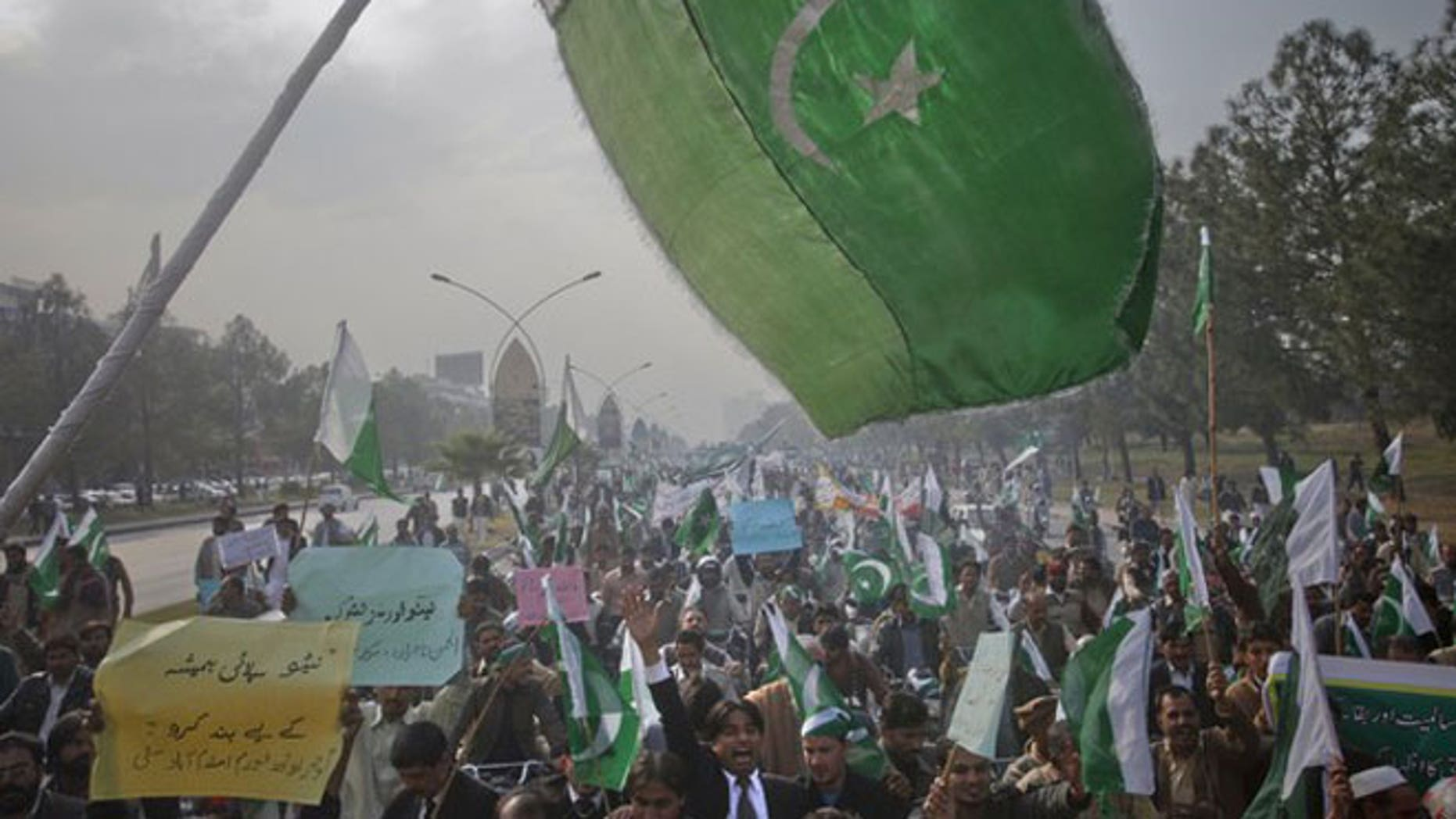 December 8, 2011: The Pakistan flag waves in the foreground as protesters hold placards during a rally in support of Pakistan army in Islamabad.