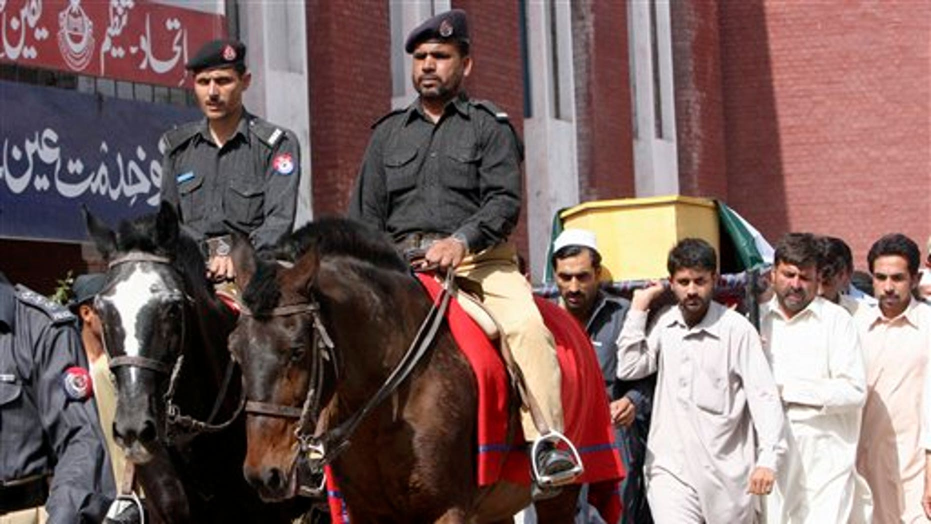 May 18: Pakistani police officers ride horses in front of  relatives of one of two officers, who were killed in an attack by militants at a security checkpoint, carrying his body during his funeral procession in Peshawar, Pakistan.