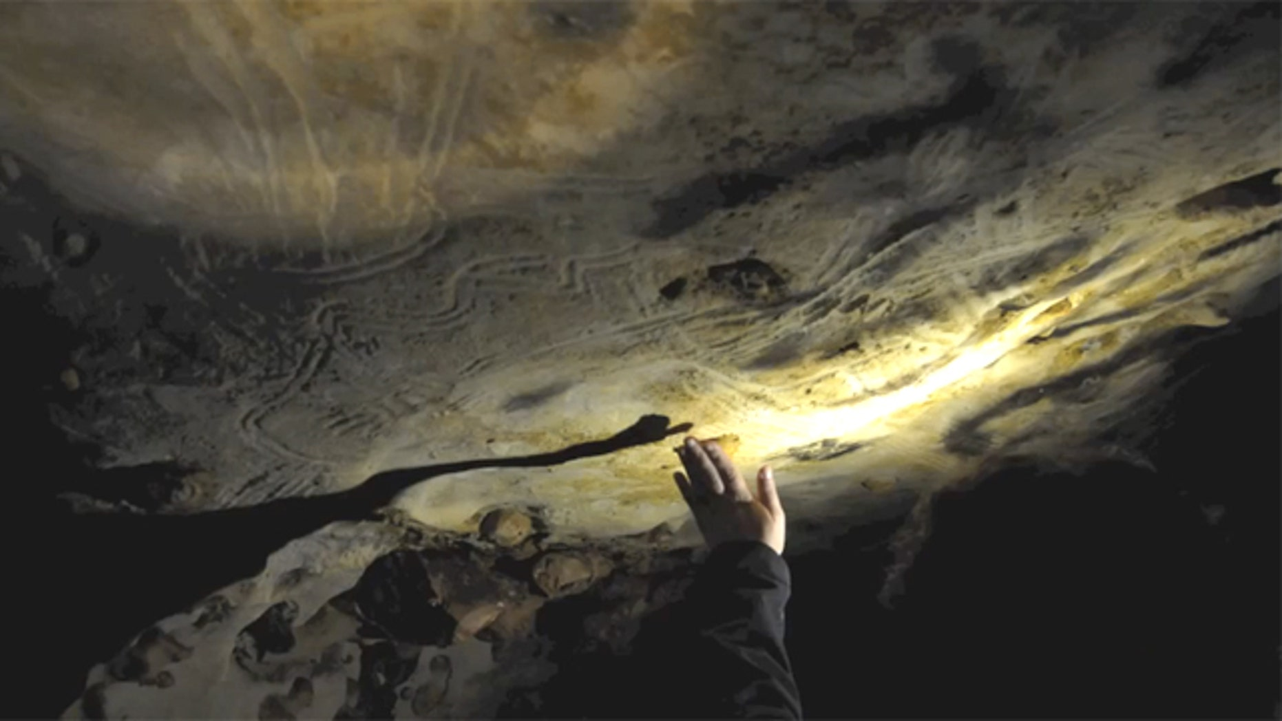"A researcher demonstrates how ancient people ""hand fluted"" the walls of a cave in France in this video still."