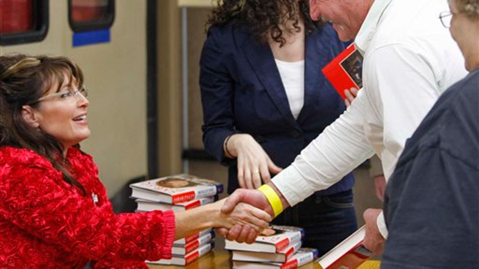 Sarah Palin shakes hands while signing books inside the Walmart in Spirit Lake, Iowa, Thursday, Dec. 2, 2010. (AP Photo/The Register, John Gaps III)