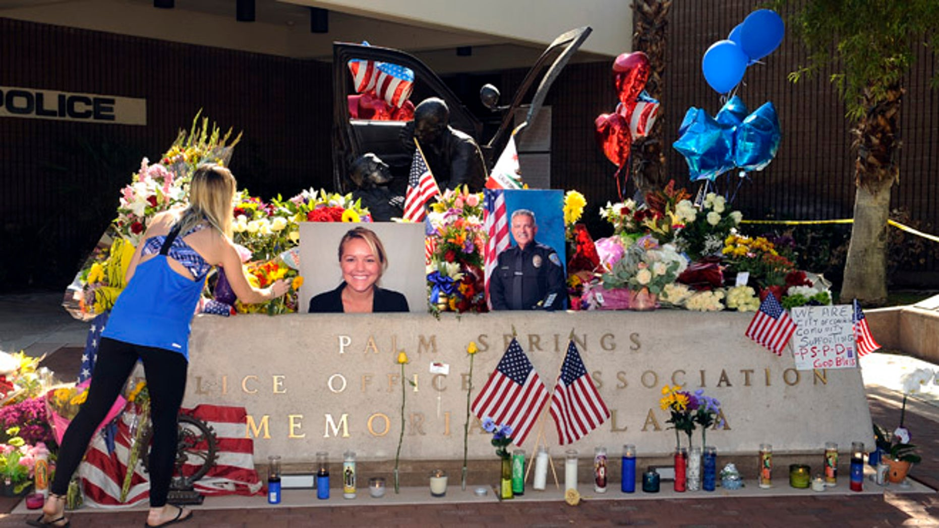 "Kimberleigh Funkey, from Palm Springs, Calif., lays flowers by photos of slain Palm Springs police officers Lesley Zerebny and Jose ""Gil"" Gilbert Vega, in front of the police station in Palm Springs, Calif., Sunday, Oct. 9, 2016. (AP Photo/Rodrigo Peña)"