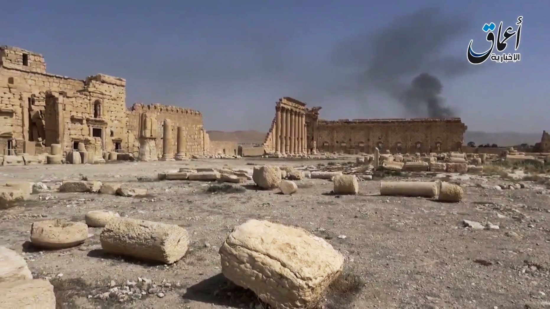 In this image made from a militant video posted on YouTube on May 26, 2015, which has been verified and is consistent with other AP reporting, smoke rises behind archaeological ruins in Palmyra, Syria. The video released by a media arm of the Islamic State group purportedly showed the archaeological ruins of Palmyra apparently undamaged.