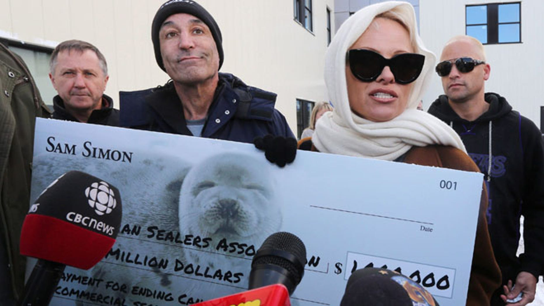 """Dec. 17, 2013: In this file photo, actress and animal activist Pamela Anderson, foreground right, and Sam Simon, producer of """"The Simpsons,"""" second left, speak to the media after attempting to deliver a letter and a million-dollar check to end the annual commercial seal hunt to the closed office of the Canadian Sealers Association in St. John's, N.L."""