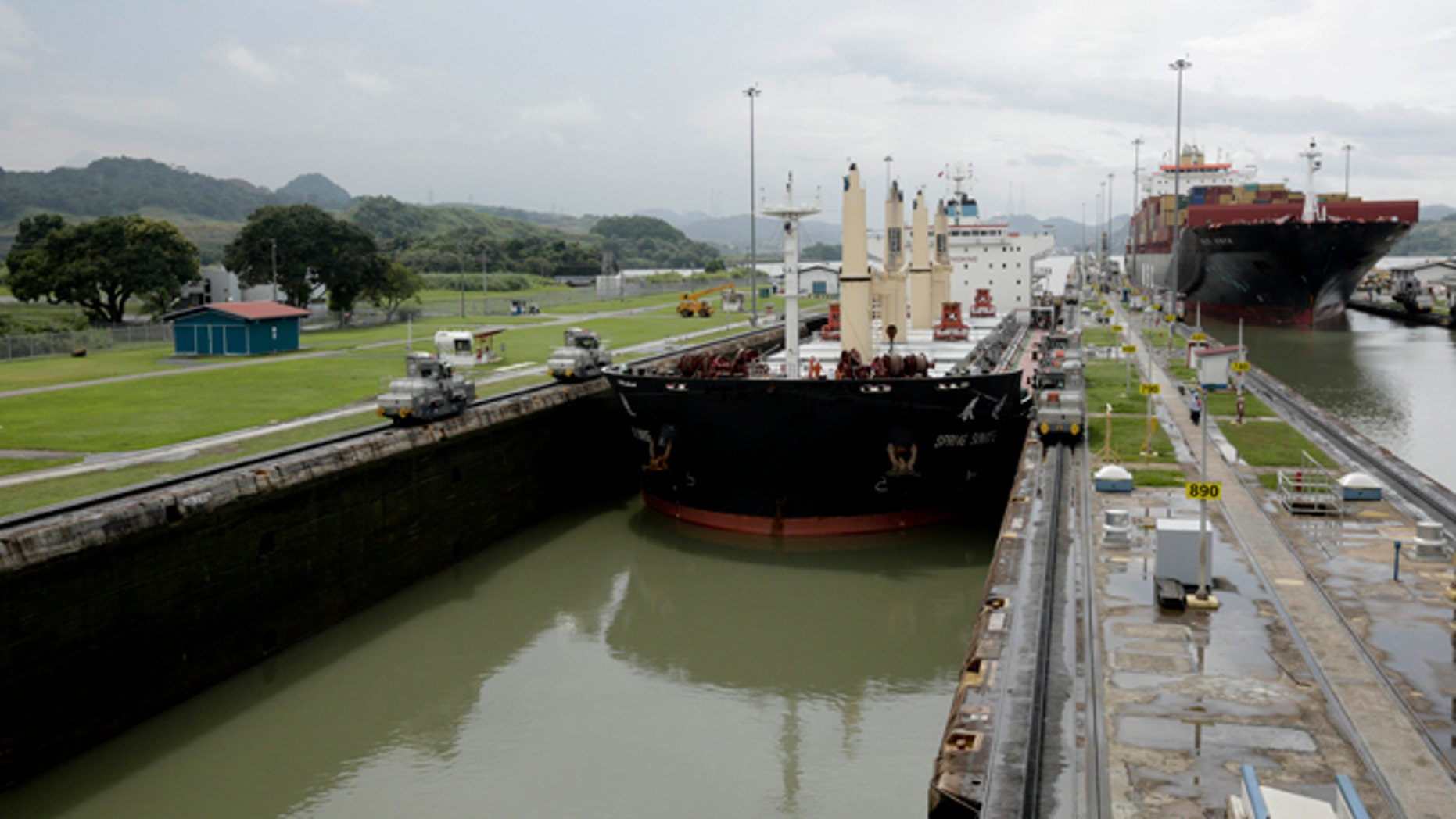 In this Aug. 4, 2014, photo, two cargo ships sails though the Miraflores locks on the Panama Canal in Panama City. (AP Photo/Arnulfo Franco)