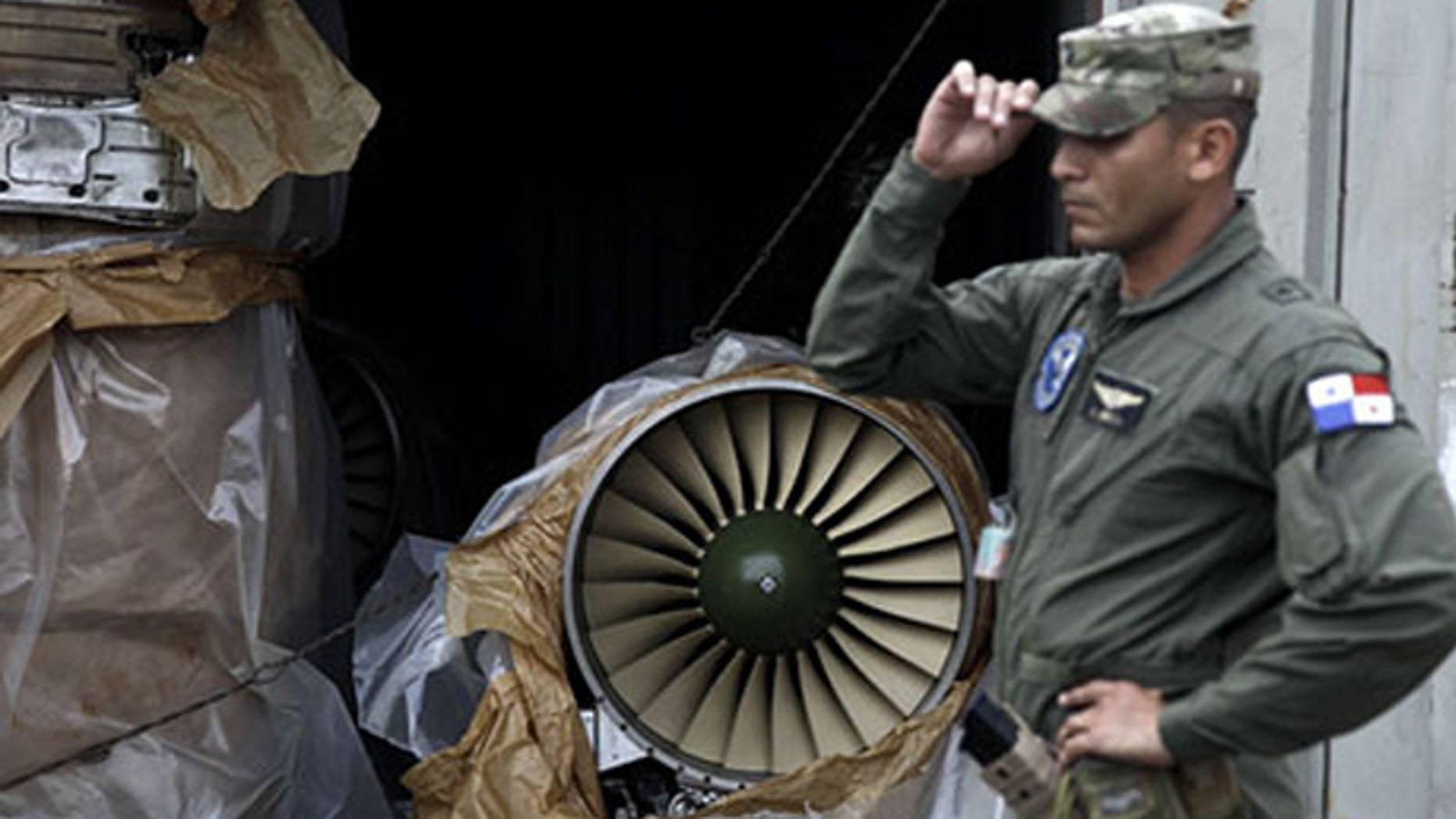 A Panamanian policeman guards a Russian fighter jet engine in one of the hidden containers discovered on a cargo ship bound from Cuba to North Korea via Panama.