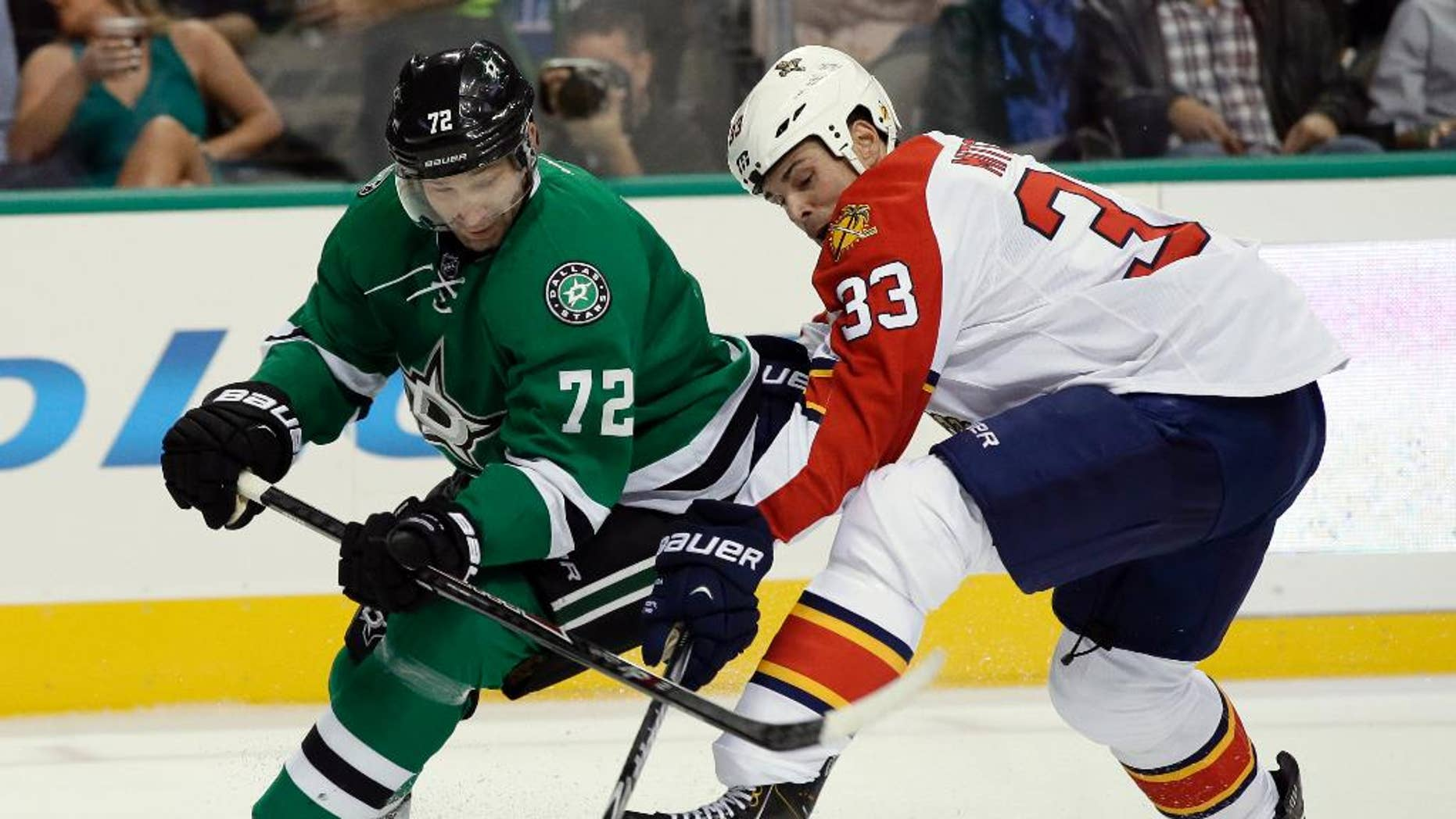 Dallas Stars' Erik Cole (72) and Florida Panthers' Willie Mitchell (33) compete for control of the puck in the first period of an preseason NHL hockey game, Monday, Sept. 29, 2014, in Dallas. (AP Photo/Tony Gutierrez)