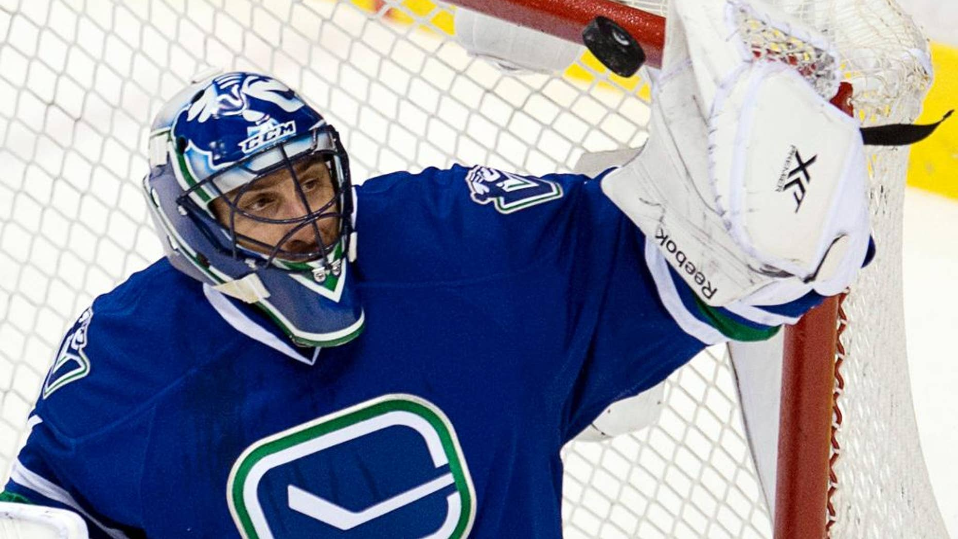 FILE - In this Jan. 29, 2014, file photo, Vancouver Canucks goalie Roberto Luongo makes a save during the first period of an NHL hockey game against the Chicago Blackhawks in Vancouver, British Columbia. Luongo was traded by the Canucks to the Panthers, who gave up goalie Jacob Markstrom and forward Shawn Mattias to make the deal happen. (AP Photo/The Canadian Press, Jonathan Hayward, File)
