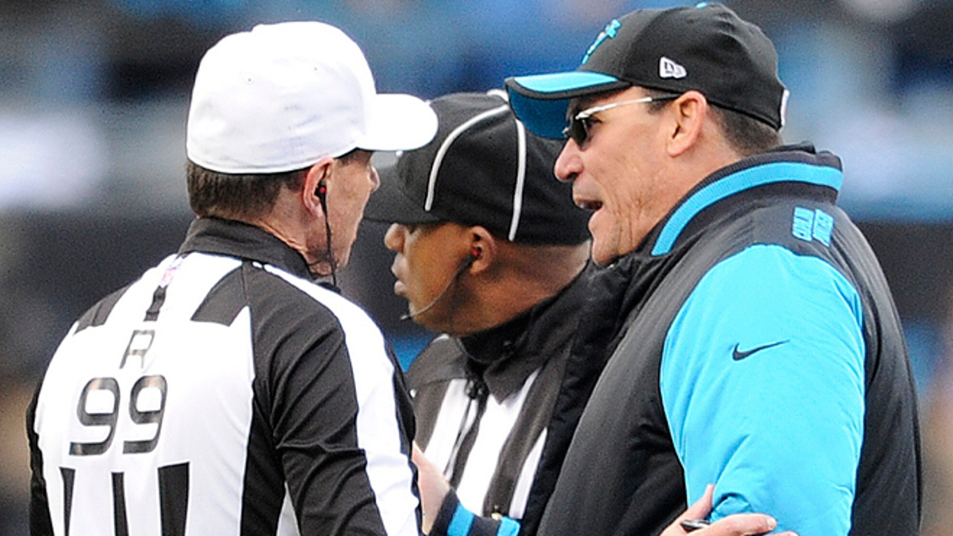 Carolina Panthers head coach Ron Rivera speaks to referee Tony Corrente (99) during the second half of an NFL divisional playoff football game against the Seattle Seahawks, Sunday, Jan. 17, 2016, in Charlotte, N.C. (AP Photo/Mike McCarn)