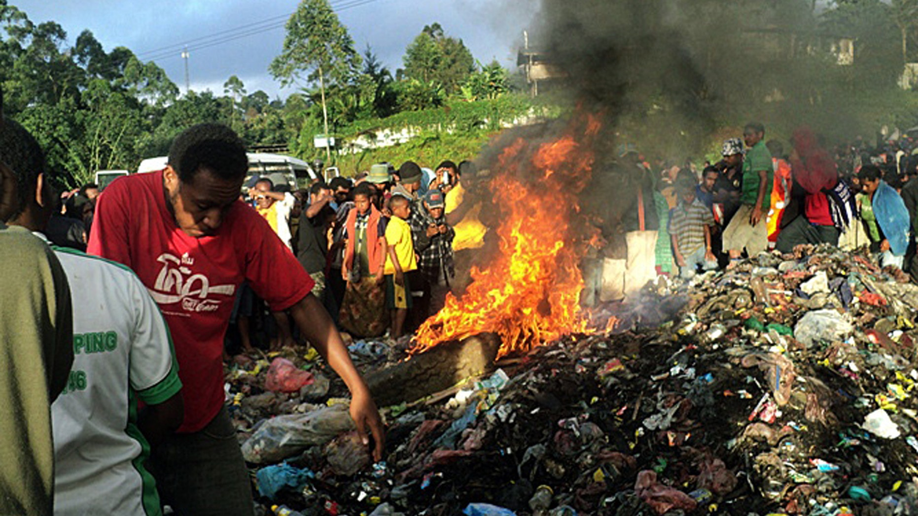 Feb. 6, 2013 - FILE photo, bystanders watch as a woman accused of witchcraft is burned alive in the Western Highlands provincial capital of Mount Hagen in Papua New Guinea.