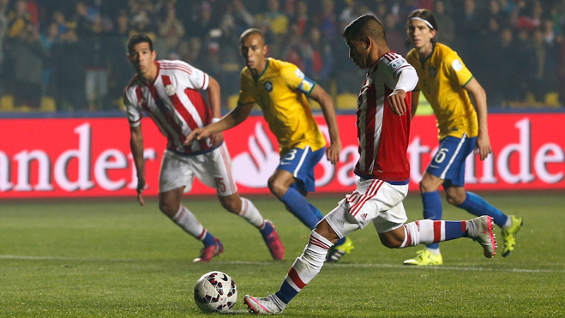 Paraguay's Derlis Gonzélez shoots from the penalty spot to scorer his sides first goal during a Copa America quarterfinal soccer match against Brazil at the Ester Roa Rebolledo Stadium in Concepción, Chile, Saturday, June 27, 2015. (AP Photo/Silvia Izquierdo)