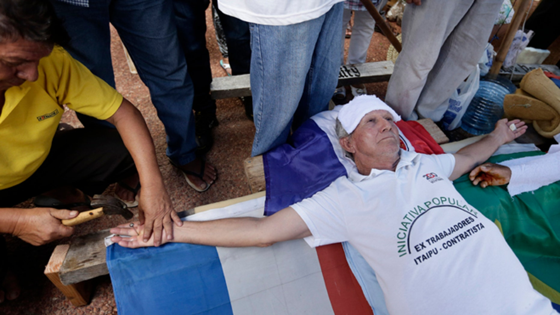 Pablo Garcete a former worker of Unicom, Conempa and Itaipu Binacional, Paraguayan Itaipu Dam contractors, is nailed to a cross in front of the Brazilian Embassy in Asuncion, Paraguay, Monday, Dec. 29, 2014. Garcete is part of a group that for the last 25 years, after the construction on the dam was completed, are symbolically crucifying themselves to demand compensation benefits from the contractors. The Itaipu hydroelectric dam on the Parana River straddles the Brazil-Paraguay border. (AP Photo/Jorge Saenz)