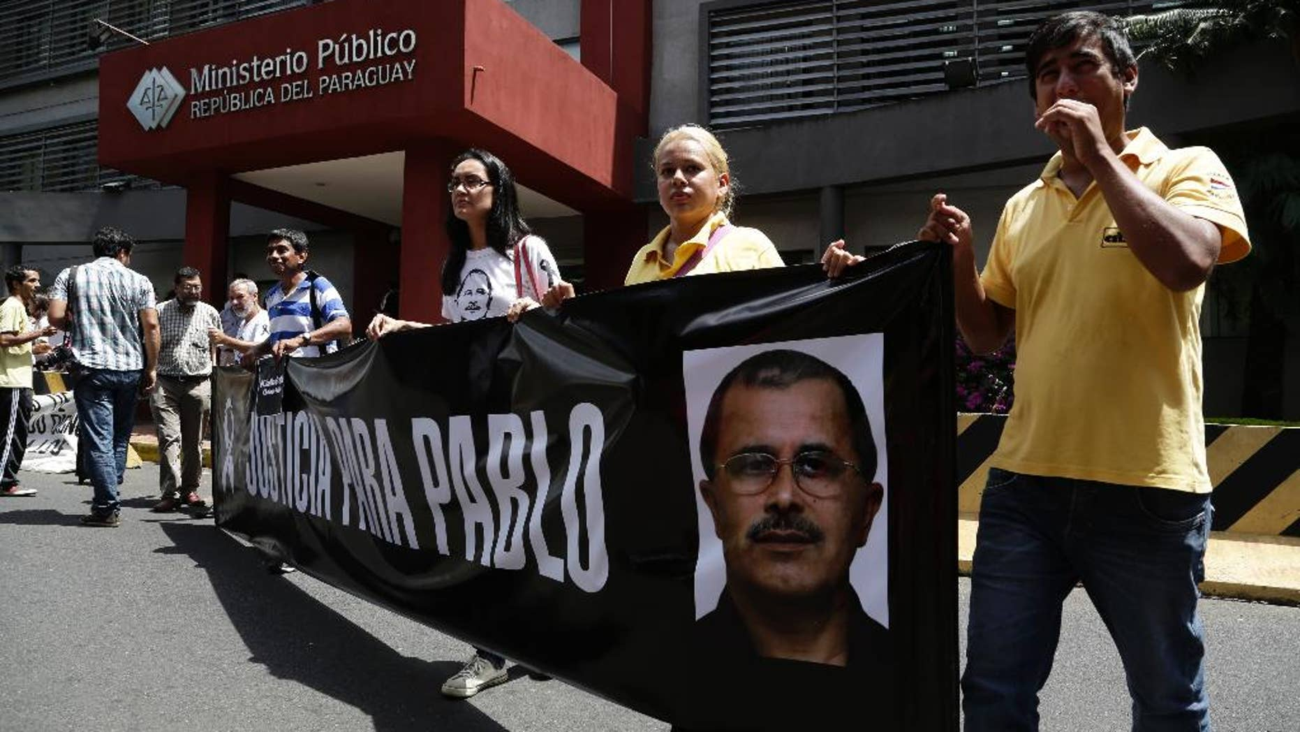 """Journalists hold a banner that shows an image of slain reporter Pablo Medina, with a message that reads in Spanish; """"Justice for Pablo"""" in a protest sparked by the death of radio journalist Gerardo Servian, outside the Attorney General's office in Asuncion, Paraguay, Friday, March 6, 2015. Medina, who focused on investigations exposing corruption and drug traffickers, was killed in October. Paraguayan officials say Servian was shot to death Thursday in a Brazilian city bordering a crime-ridden area that is a hotbed for drugs and arms smuggling. (AP Photo/Jorge Saenz)"""