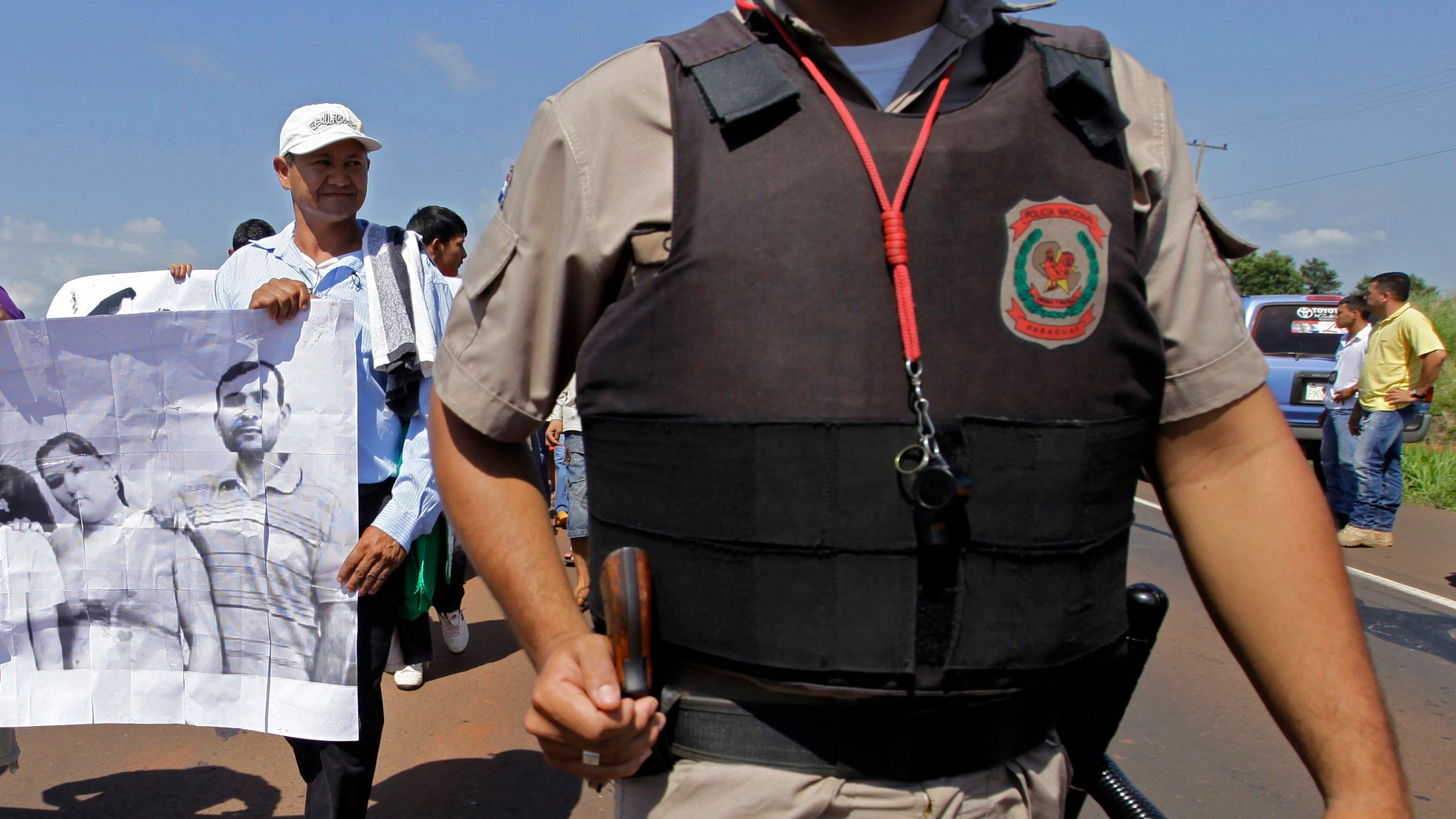 In this photo taken Nov. 15 2012 Vidal Vega, left,  holds a banner during a march to demand the freedom of landless farmers near Curuguaty city, Paraguay. (AP Photo/Jorge Saenz)