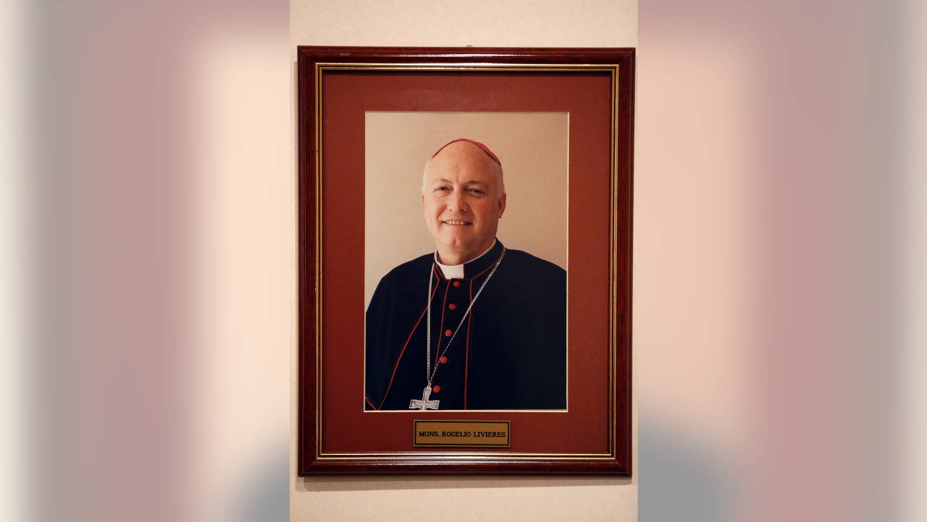 FILE - This May 13, 2015 file photo shows a framed portrait of the ousted Bishop Rogelio Livieres Plano, that hangs on an office wall in Paraguay's Ciudad del Este diocese. The former Paraguayan bishop who was ousted by Pope Francis amid several controversies in his diocese has died of problems related to diabetes in a Buenos Aires hospital, Friday, Aug. 14, 2015. Livieres Plano was 69. (AP Photo/Jorge Saenz, File)