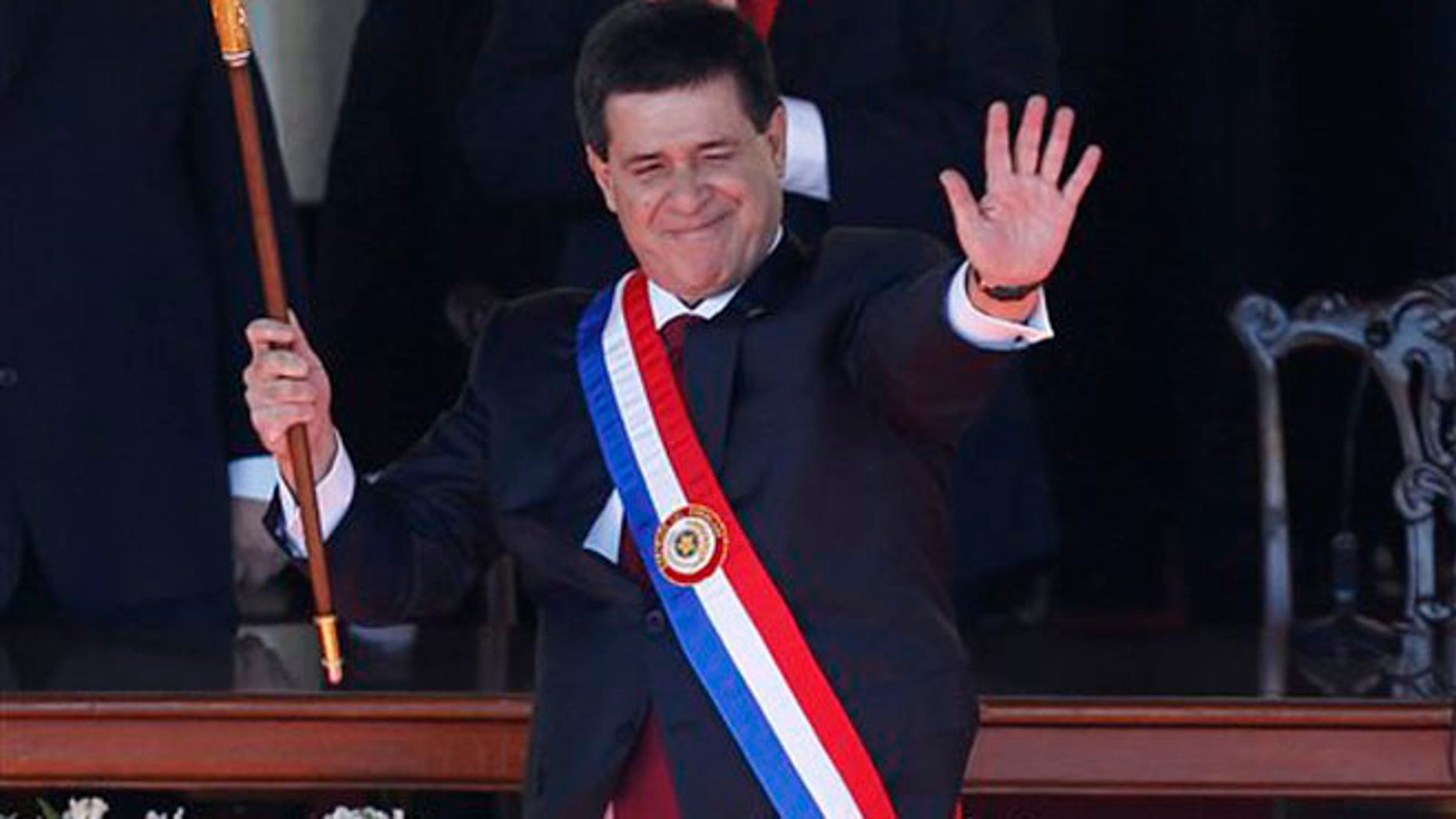 Paraguay's New President Horacio Cartes waves holding the presidential baton and wearing the presidential sash during his swearing-in ceremony at Palacio de Lopez presidential palace in Asuncion, Paraguay, Thursday, Aug. 15, 2013.