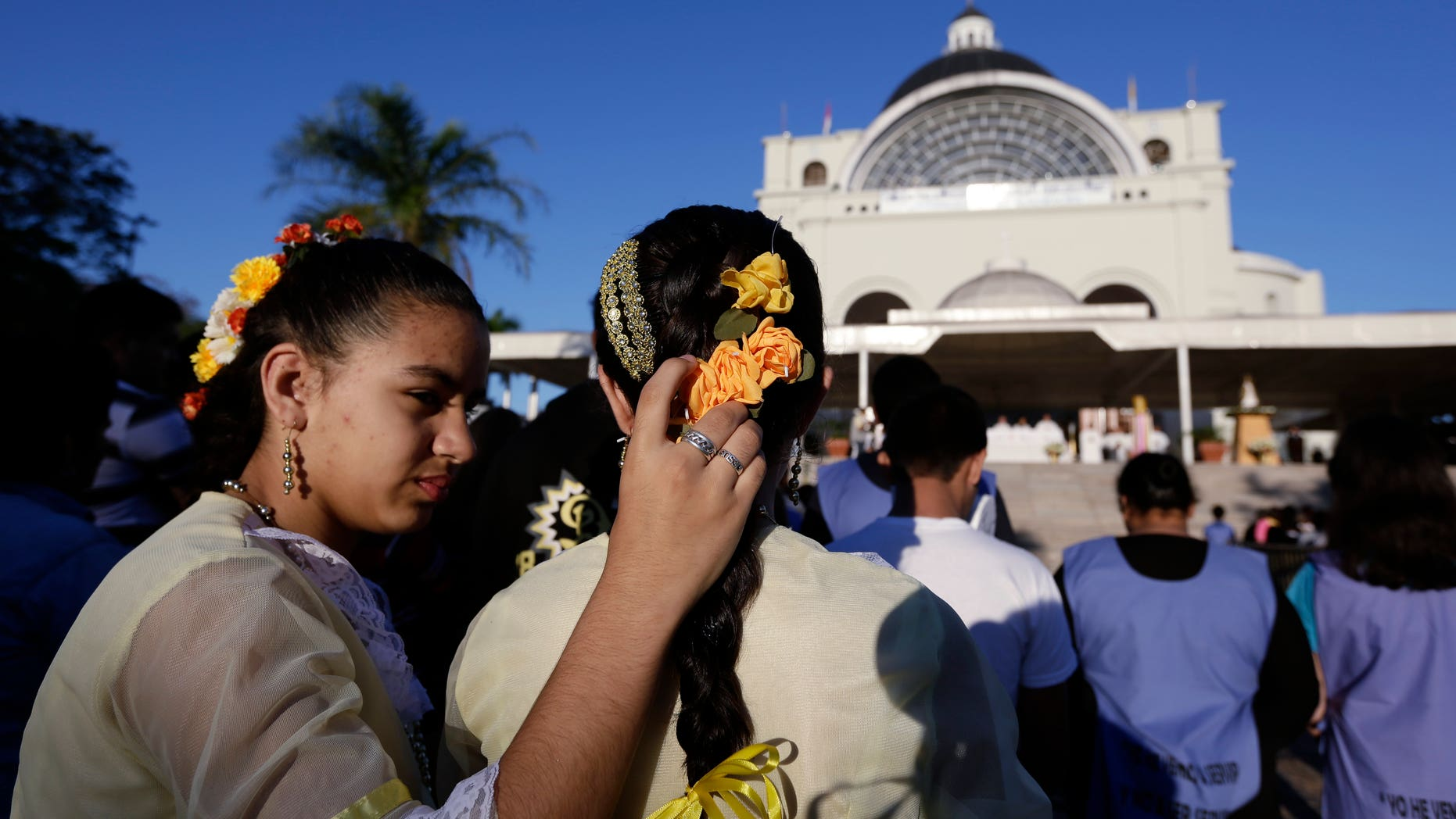 Two sisters during a Corpus Christi mass at shrine of the Virgin of Miracles in Caacupe, Paraguay.