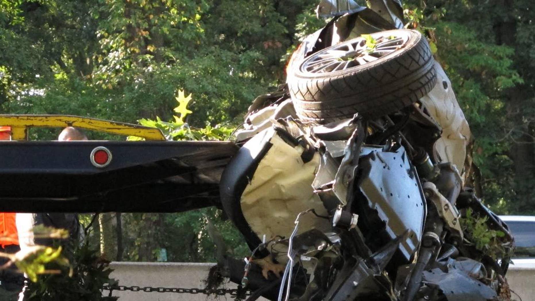 FILE - In this Oct. 8, 2012 file photo, a wrecked car is loaded onto a flatbed truck on the Southern State Parkway in West Hempstead, N.Y., after four people died in an early-morning accident. Joseph Beer, a New York City teenager who admitted being high on marijuana and speeding when he slammed into a tree, was convicted of four counts of vehicular manslaughter in the deaths of his friends, returns to court on Tuesday July 29, 2014 to hear if a prosecutor will retry him on aggravated vehicular homicide charges. (AP Photo/Frank Eltman, File)