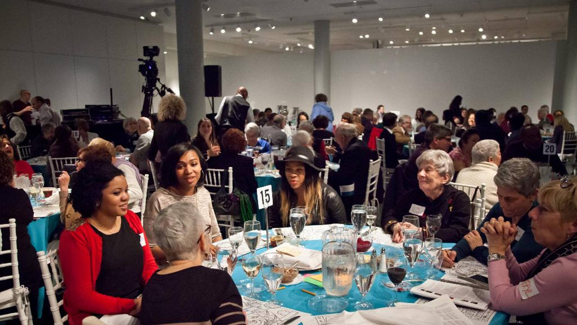 In this Wed., March 25, 2015 photo provided by Matthew Christopher, participants attend Freedom Seder Revisited at the National Museum of American Jewish History in Philadelphia. The event embraces gentiles for an evening of storytelling, music and a taste of traditional Passover food and rituals as it honors the original interfaith Freedom Seder held in 1969 in Washington, D.C., on the first anniversary of Martin Luther King Jr.'s assassination. (AP Photo/Courtesy Matthew Christopher)