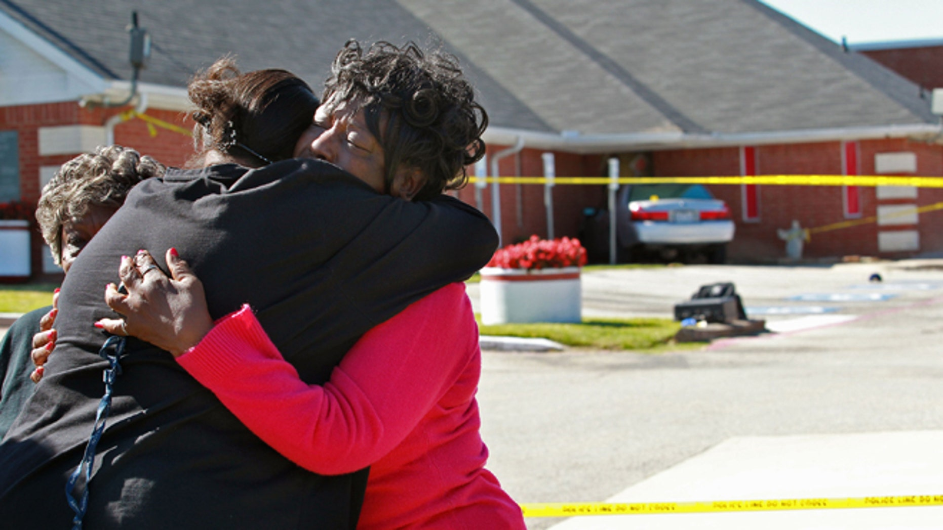 Oct. 29, 2012: People comfort one another outside of the Greater Sweethome Missionary Baptist Church in Forest Hill, Texas, after the church's founding pastor was killed Monday by an attacker who rammed a car, seen in background, into a church wall, chased the pastor and beat him with an electric guitar, according to police.