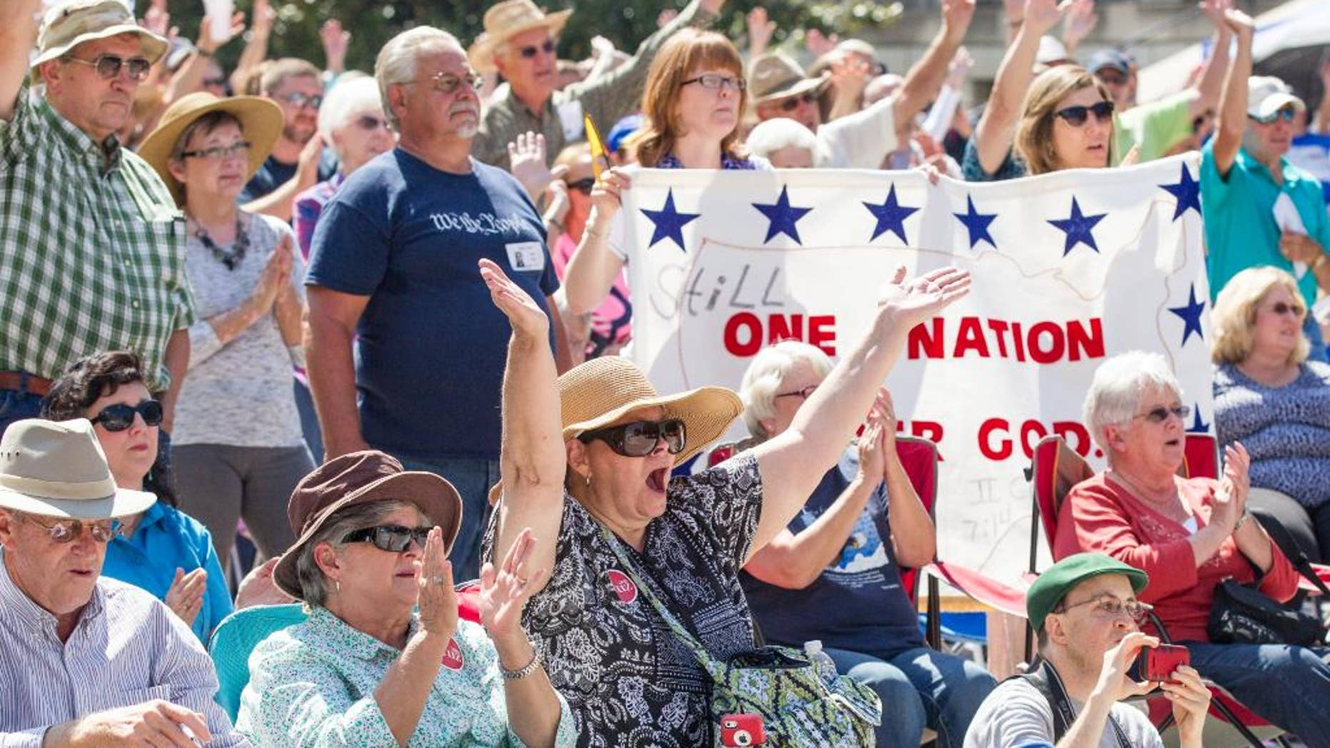 Members of the crowd cheer during a Christian conservatives rally outside the Tennessee Capitol on Thursday, Sept. 17, 2015, in Nashville. The event featured Joe Davis, the husband of Kentucky clerk Kim Davis, and Rafael Cruz, the father of U.S. Sen. Ted Cruz, a Republican presidential candidate. (AP Photo/Erik Schelzig)