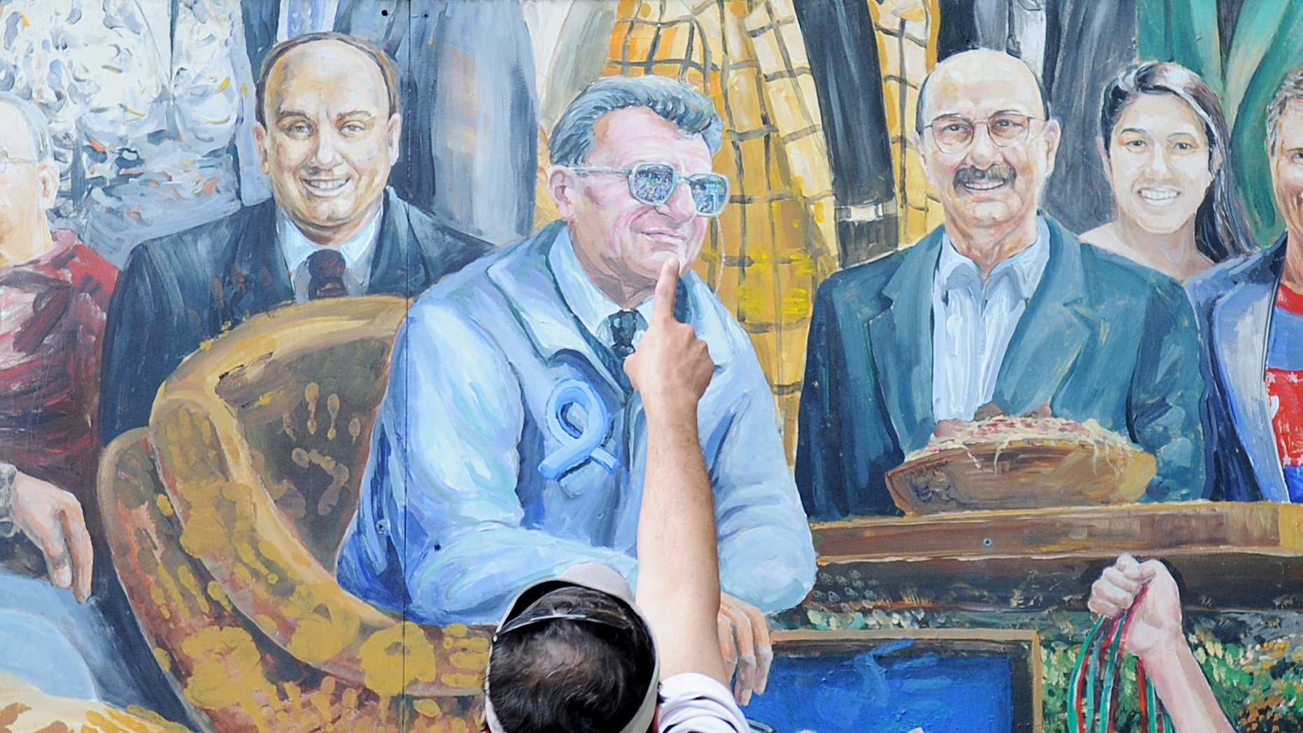 July 14, 2012: A visitor points to the spot in a mural by Michael Pilato where a halo that was above the late Penn State football coach Joe Paterno has been painted over by the artist in State College, Pa.