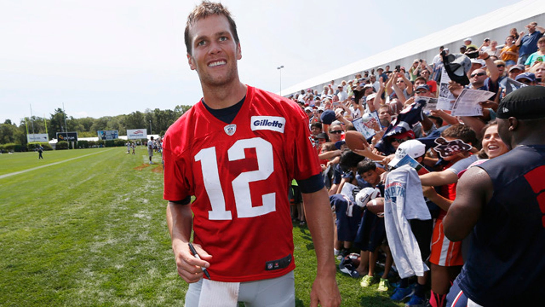 Aug. 1, 2015: New England Patriots quarterback Tom Brady walks down the line of fans signing autographs during an NFL football training camp in Foxborough, Mass. (AP Photo/Michael Dwyer)