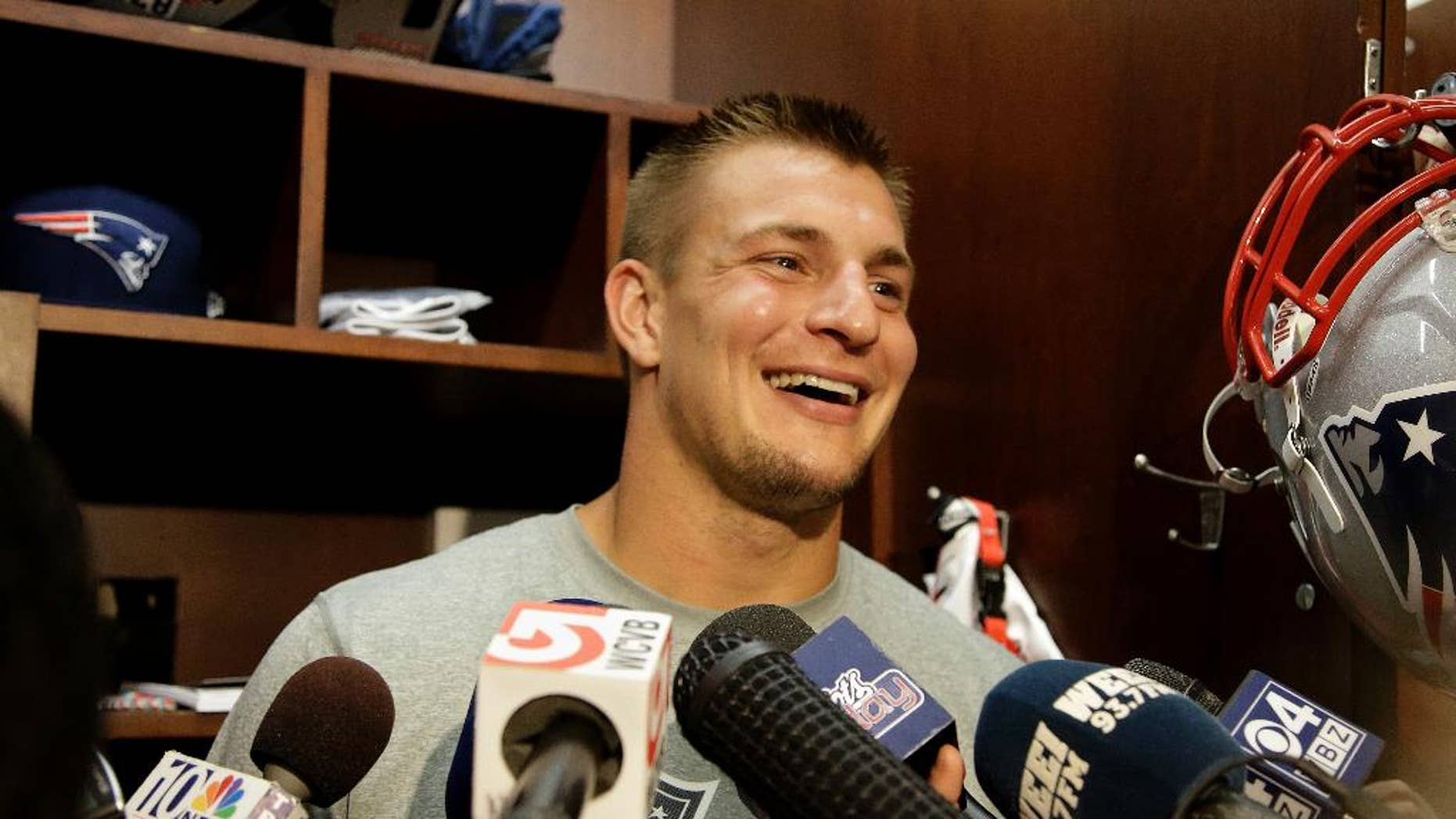FILE - This Sept. 4, 2013, file photo shows New England Patriots tight end Rob Gronkowski smiling as he talks to the media at the NFL football team's facility in Foxborough, Mass. Gronkowski stood in front of his Gillette Stadium locker Monday, Sept. 1, 2014, and announced he will be playing in the New Patriots' opener at Miami this Sunday. (AP Photo/Stephan Savoia, File)