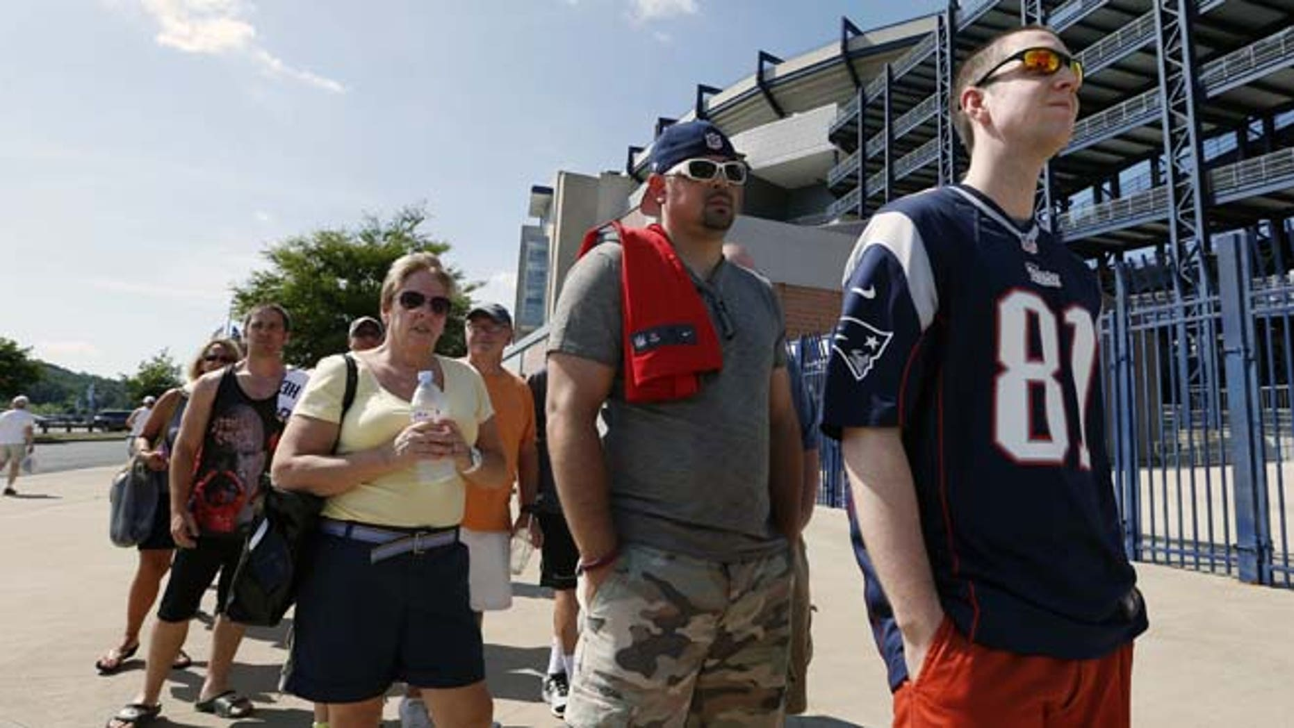 July 6, 2013: Mike Davies, right, of Norfolk, Mass., wears his New England Patriots Aaron Hernandez football jersey one last time while waiting in an exchange line outside Gillette Stadium in Foxborough, Mass. Fans may trade an Aaron Hernandez jersey with his name on it they purchased for one of another player on the NFL team. The team released Hernandez after he was arrested for allegedly orchestrating the death of Odin Lloyd.