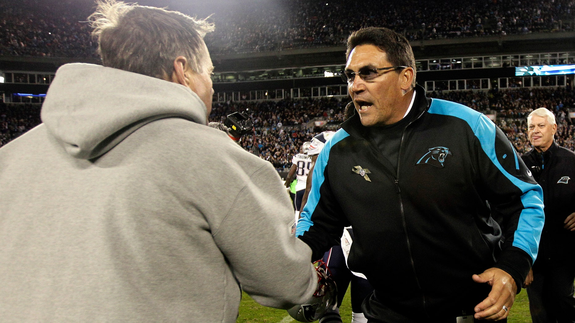 New England Patriots head coach Bill Belichick, left, and Carolina Panthers head coach Ron Rivera shake hands following an NFL football game in Charlotte, N.C., Monday, Nov. 18, 2013. Carolina won 24-20. (AP Photo/Gerry Broome)