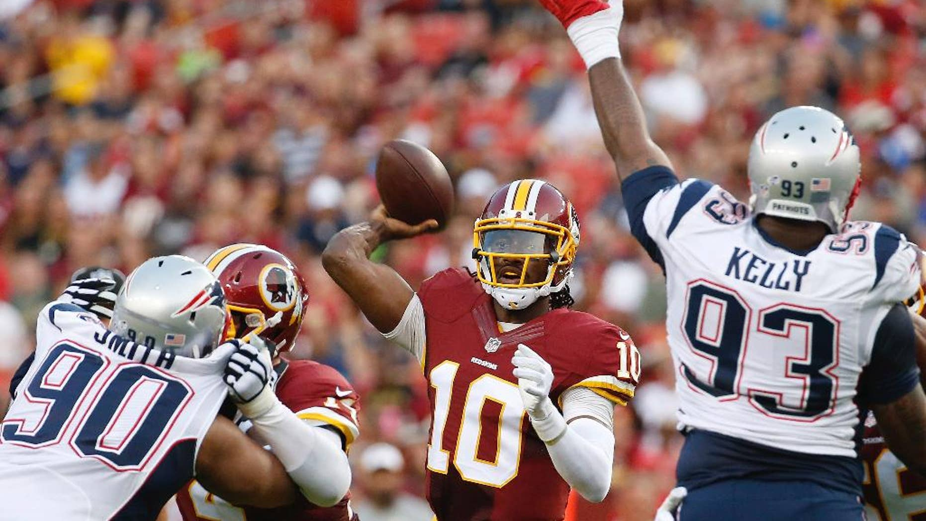 Washington Redskins quarterback Robert Griffin III passes between New England Patriots defensive end Will Smith (90) and defensive tackle Tommy Kelly (93) during the first half of an NFL football preseason game in Landover, Md., Thursday, Aug. 7, 2014. (AP Photo/Alex Brandon)