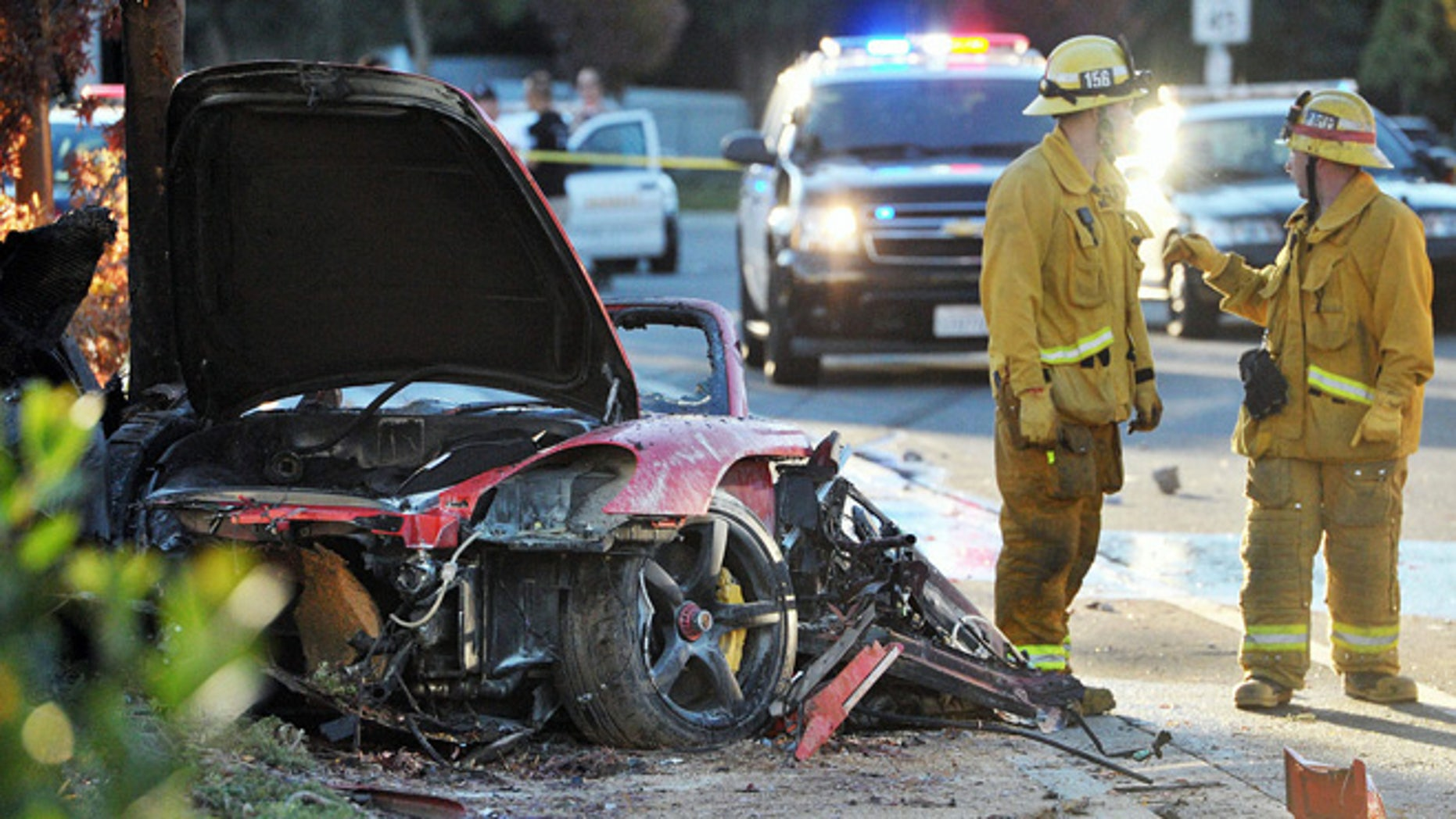 "FILE - In this Nov. 30, 2013 file photo, firefighters stand near the wreckage of a Porsche that hit a light pole and burned on Hercules Street near Kelly Johnson Parkway in Valencia, Calif., a crash that killed actor Paul Walker and his friend Roger Rodas.  A law enforcement official with knowledge of the investigation told The Associated Press Wednesday, Dec. 18, 2013, that the car lost control due to ""speed, and speed alone."" Investigators have found no evidence that the Porsche carrying the ""Fast & Furious"" actor had mechanical problems before it crashed. (AP Photo/The Santa Clarita Valley Signal, Dan Watson, File)"