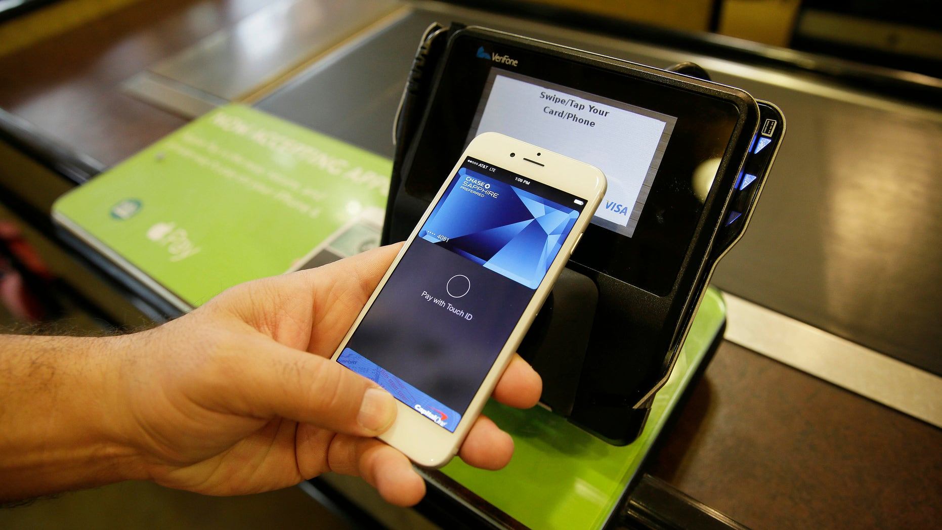 In this photo taken Friday, Oct. 17, 2014, Eddy Cue, Apple Senior Vice President of Internet Software and Services, demonstrates the new Apple Pay mobile payment system at a Whole Foods store in Cupertino, Calif. The new system launches on Monday. (AP Photo/Eric Risberg)