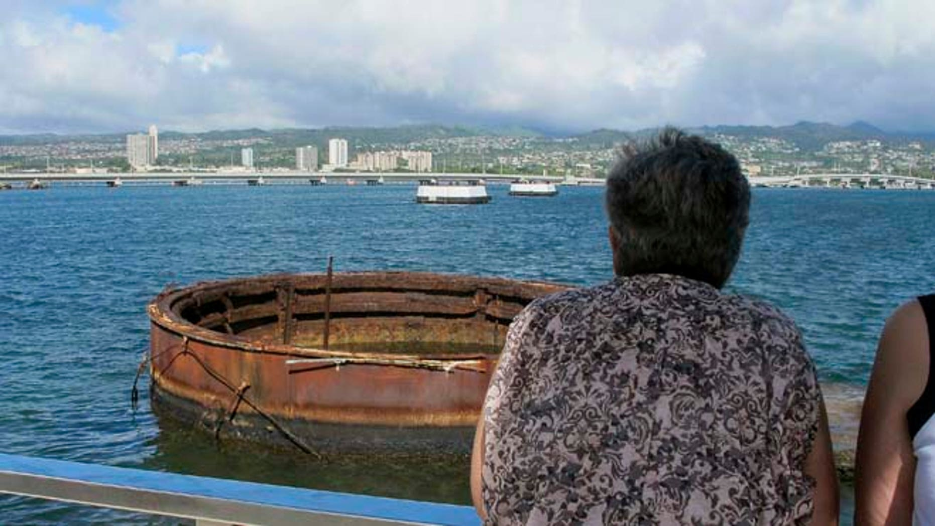 This Nov. 21, 2014 photo shows visitors looking out at the sunken USS Arizona from a memorial atop the rusting battleship in Pearl Harbor, Hawaii. (AP)