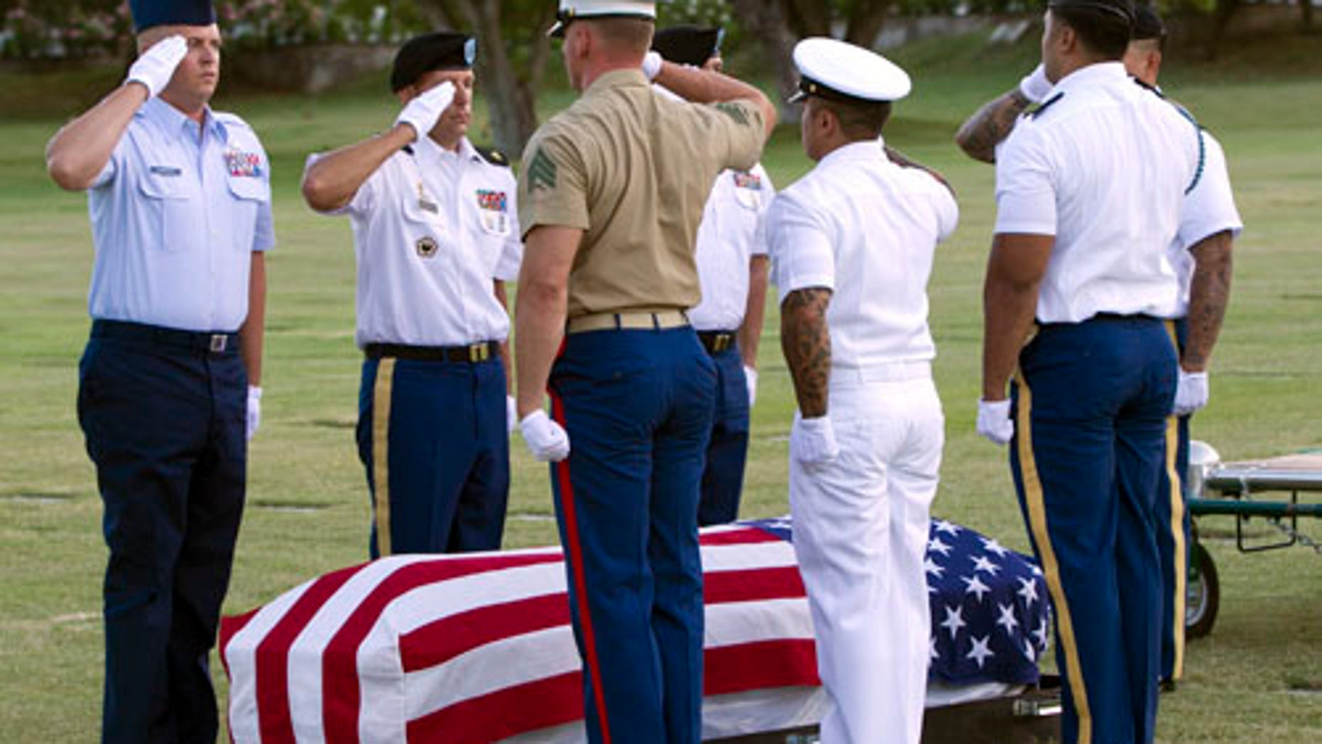 In this photo taken July 27, 2015, in Honolulu, military pallbearers salute over the exhumed remains of unidentified crew members of the USS Oklahoma killed in the Dec. 7, 1941, bombing of Pearl Harbor. The military says it has identified the remains of seven crew members missing since the Oklahoma capsized in the bombing. (AP Photo/Marco Garcia)