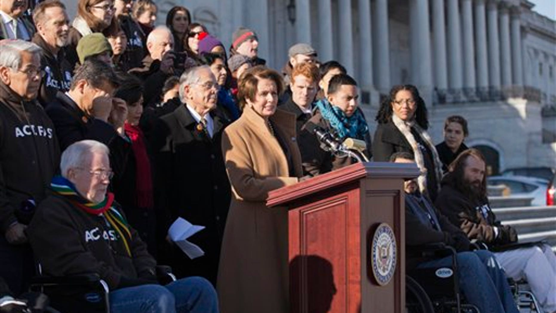 "FILE - In this Dec. 12, 2013, file photo House Minority Leader, Democrat Nancy Pelosi of California, at the podium, is joined by Congressional Hispanic Caucus Chairman Rep. Ruben Hinojosa, D-Texas, to her left, as she calls for action on immigration reform on Capitol Hill in Washington with other lawmakers and activists. Democrats are planning to rely on an infrequently used and rarely successful tactic to shine an election-year spotlight on Republican opposition to raising the minimum wage and overhauling immigration laws: its known as a ""discharge petition. It requires the minority party to persuade some two dozen Republicans to defy their leadership. (AP Photo/J. Scott Applewhite, File)"