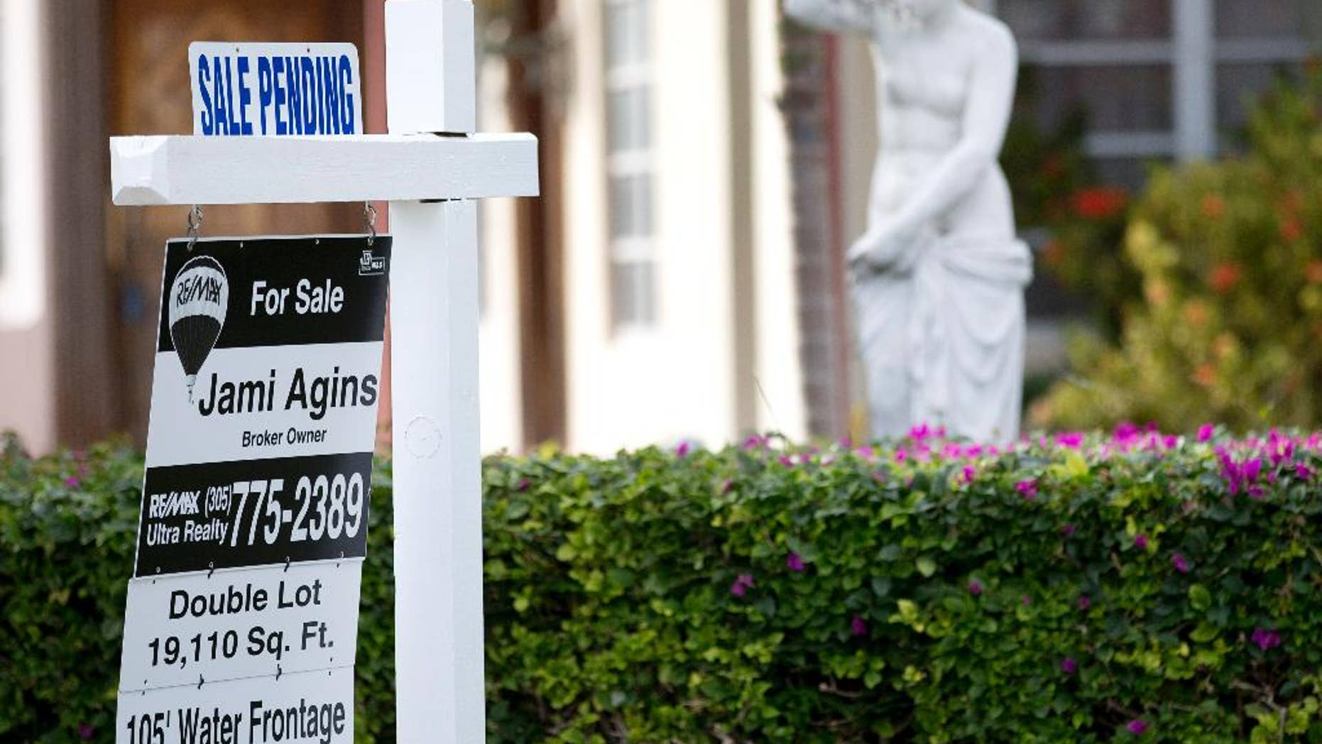 """In this Thursday, Jan. 8, 2015 photo, a """"sale pending"""" placcard is placed atop a realty sign outside a home for sale in Surfside, Fla. More Americans signed contracts to buy homes in February, the National Association of Realtors reported Monday, March 30, 2015, evidence that the spring buying season could open strong after sluggish sales for much of the winter. (AP Photo/Wilfredo Lee)"""