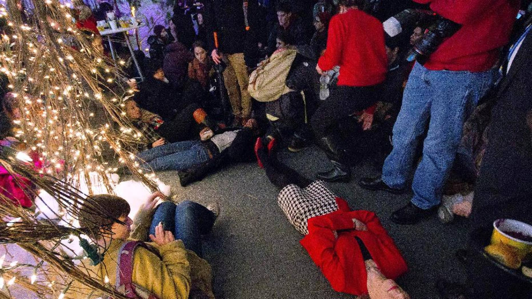 "In this Tuesday, Dec. 9, 2014 photo provided by The Daily Pennsylvanian, University of Pennsylvania President Amy Gutmann joins protesters at a holiday party at her home in Philadelphia, lying on the floor for a symbolic 4½ minute ""die-in"" to protest the police-shooting death of Michael Brown in Ferguson, Mo. The head of the campus police union said officers were outraged by Gutmann's display after student protesters interrupted her holiday party. A Penn vice president said Guttmann was showing solidarity with students, not attacking officers. (AP Photo/The Daily Pennsylvanian, Luke Chen)"